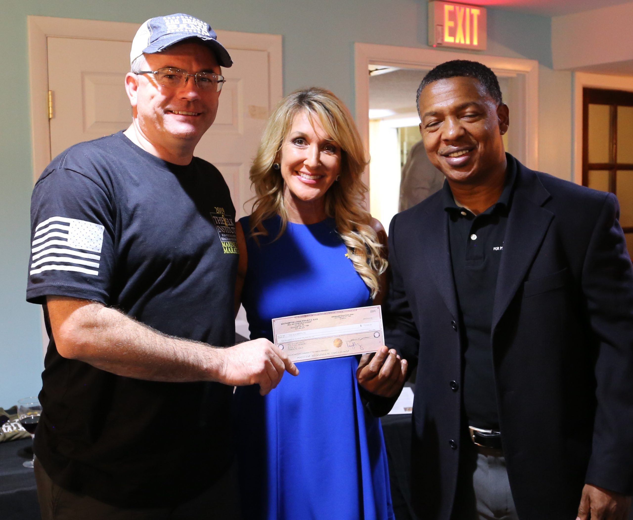 On behalf of Southampton Elks Lodge #1574, Ken Rothwell, left, presents a check to Dr. Carrie Elk, center,  and the Elk Institute vice president Major Raymond Sterling.