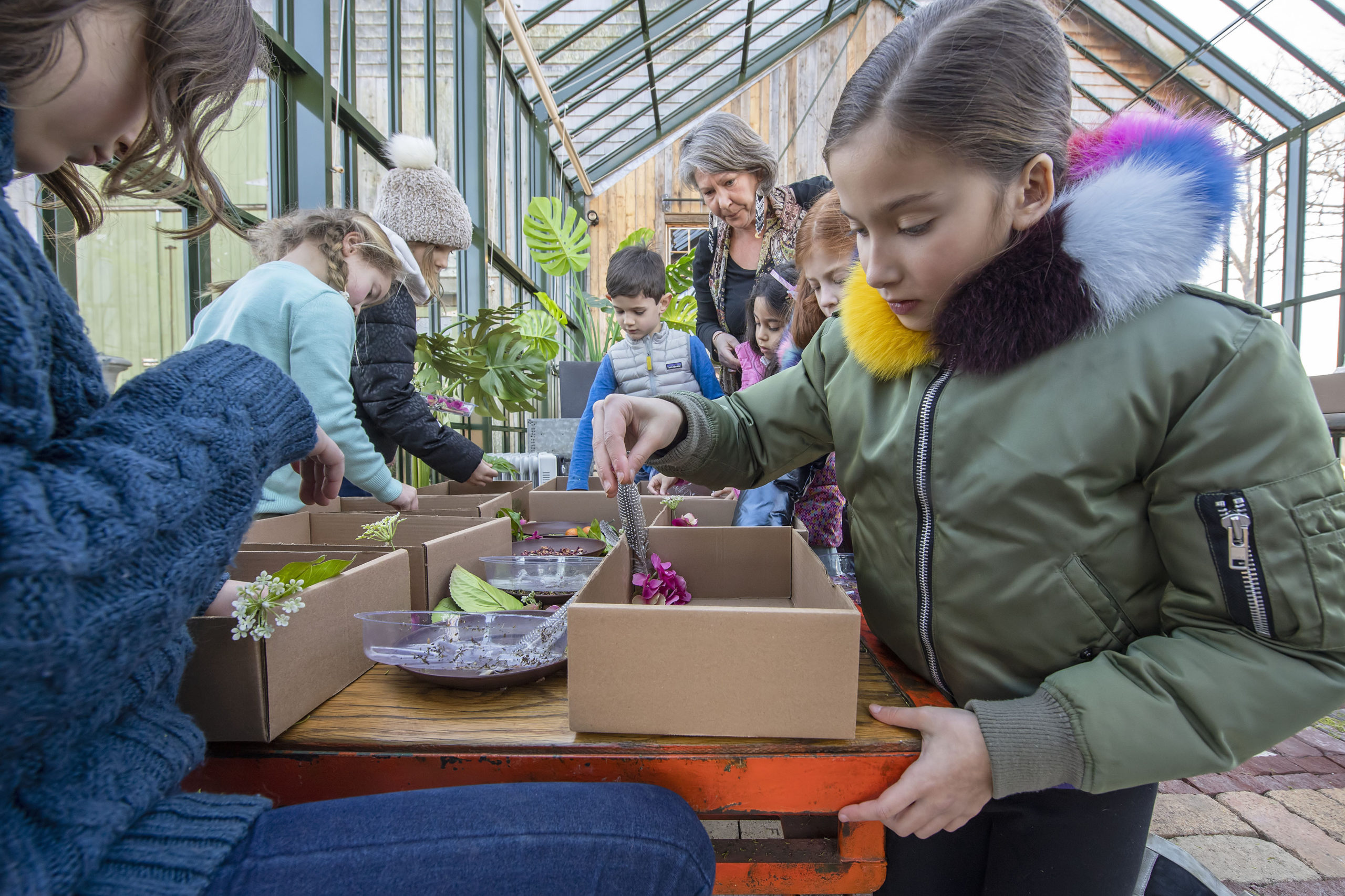 Sarah Shepard of Marders Nursery guides a group of children on how to create a Fairy Garden in a box at Marders Nursery on Saturday afternoon.   MICHAEL HELLER