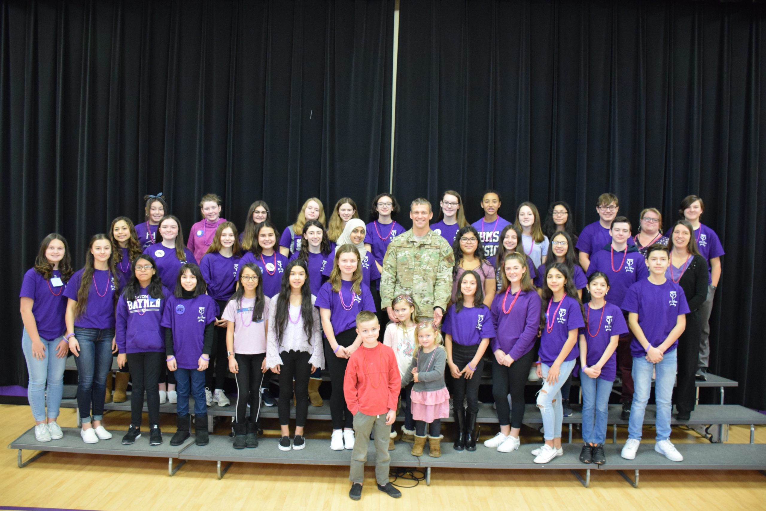 Hampton Bays High School students honored Senior Master Sergeant Erik S. Blom during a flag ceremony on February 14. With him are his children, Ryder, Sydney and Taylor, surrounded by the school's chorus.