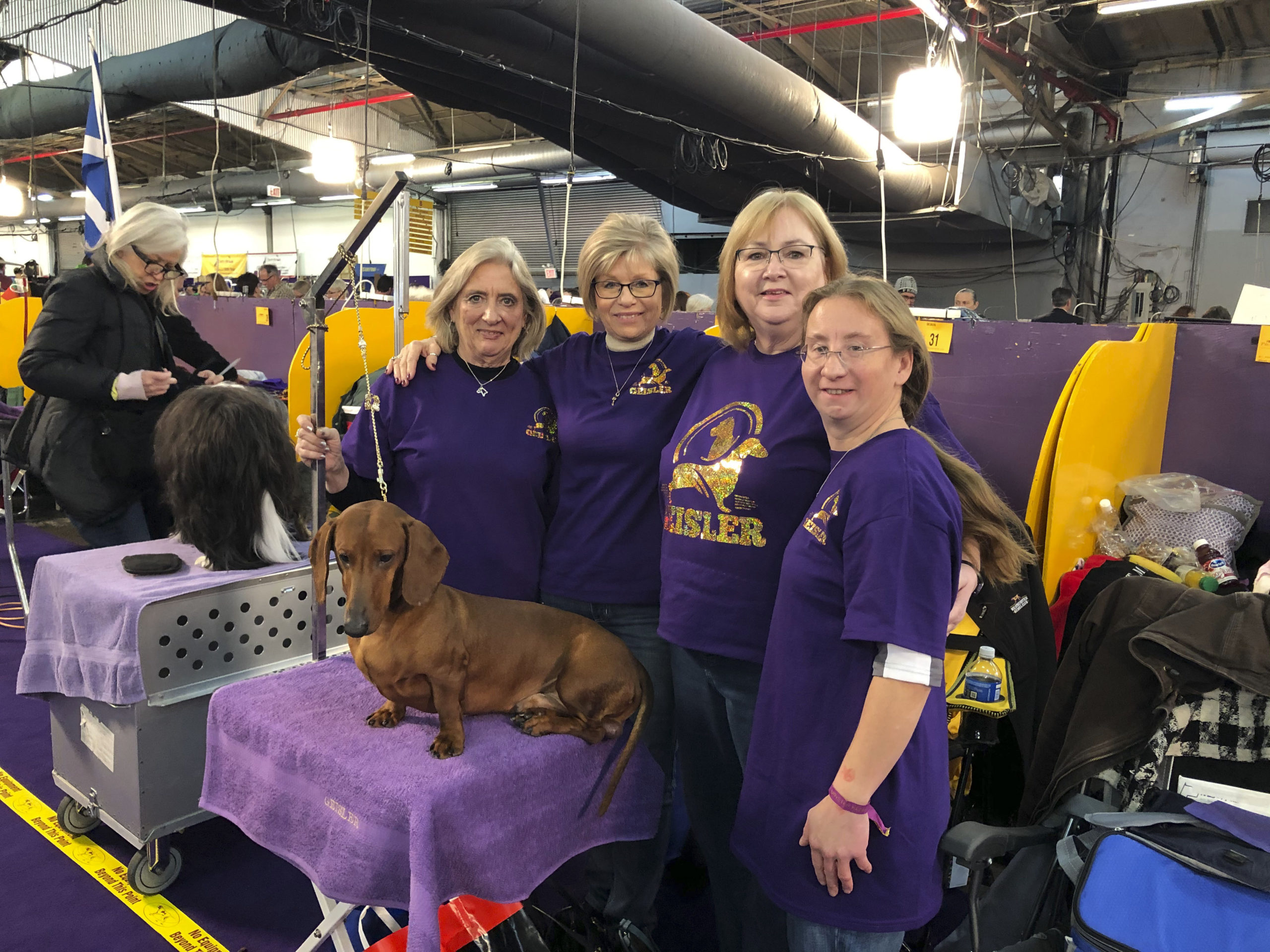 Southampton High School alum Alex Geisler, far right, with her Smooth Haired dachshund, Hammer, in the benching area of the Westminster Dog Show. SHELLY BORKOSKI