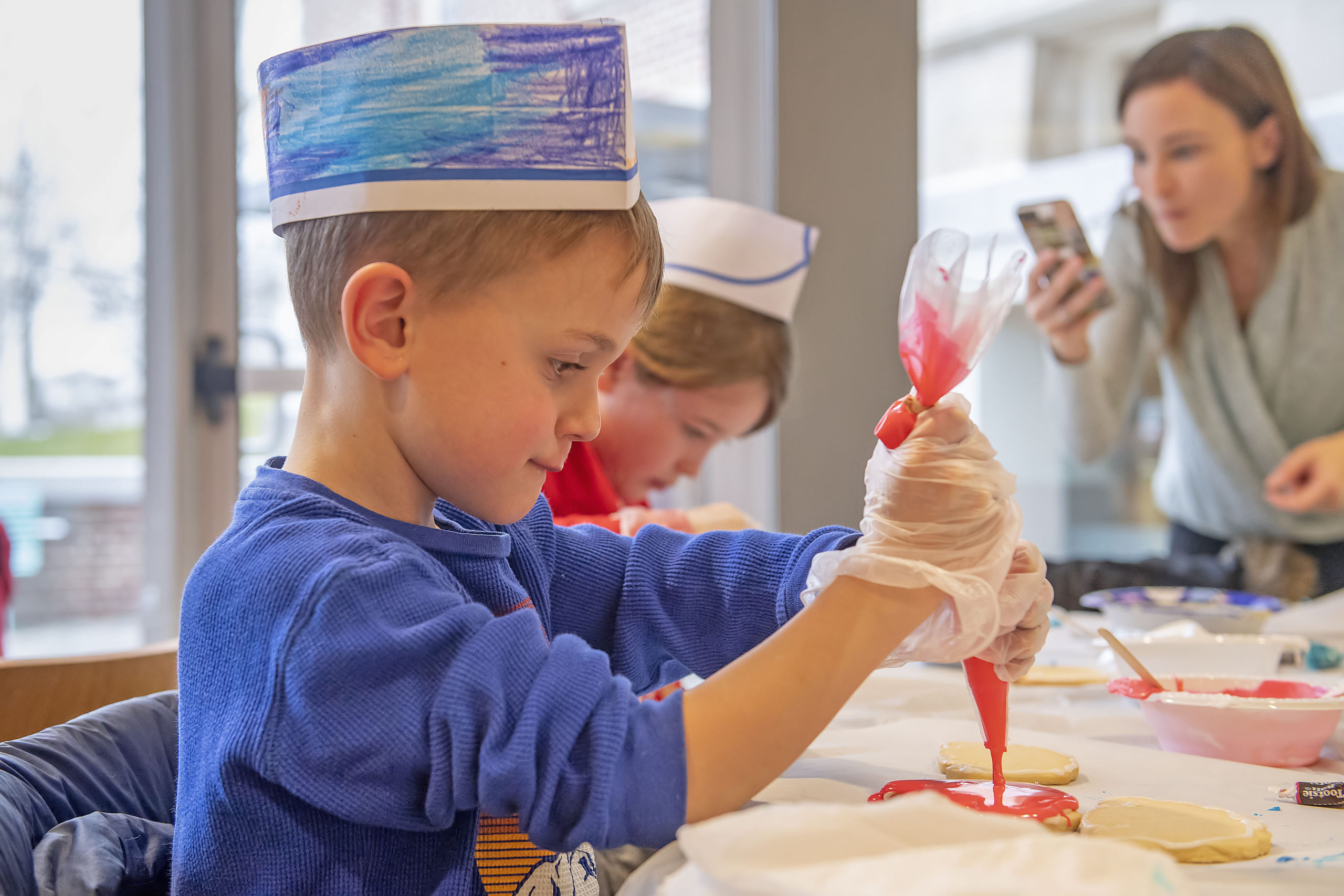Six-year-old Henry Rozzi is a study in concentration as she applies some icing during a Football Jersey Cookie Decorating Workshop that was held at the John Jermain Library on Saturday.    MICHAEL HELLER