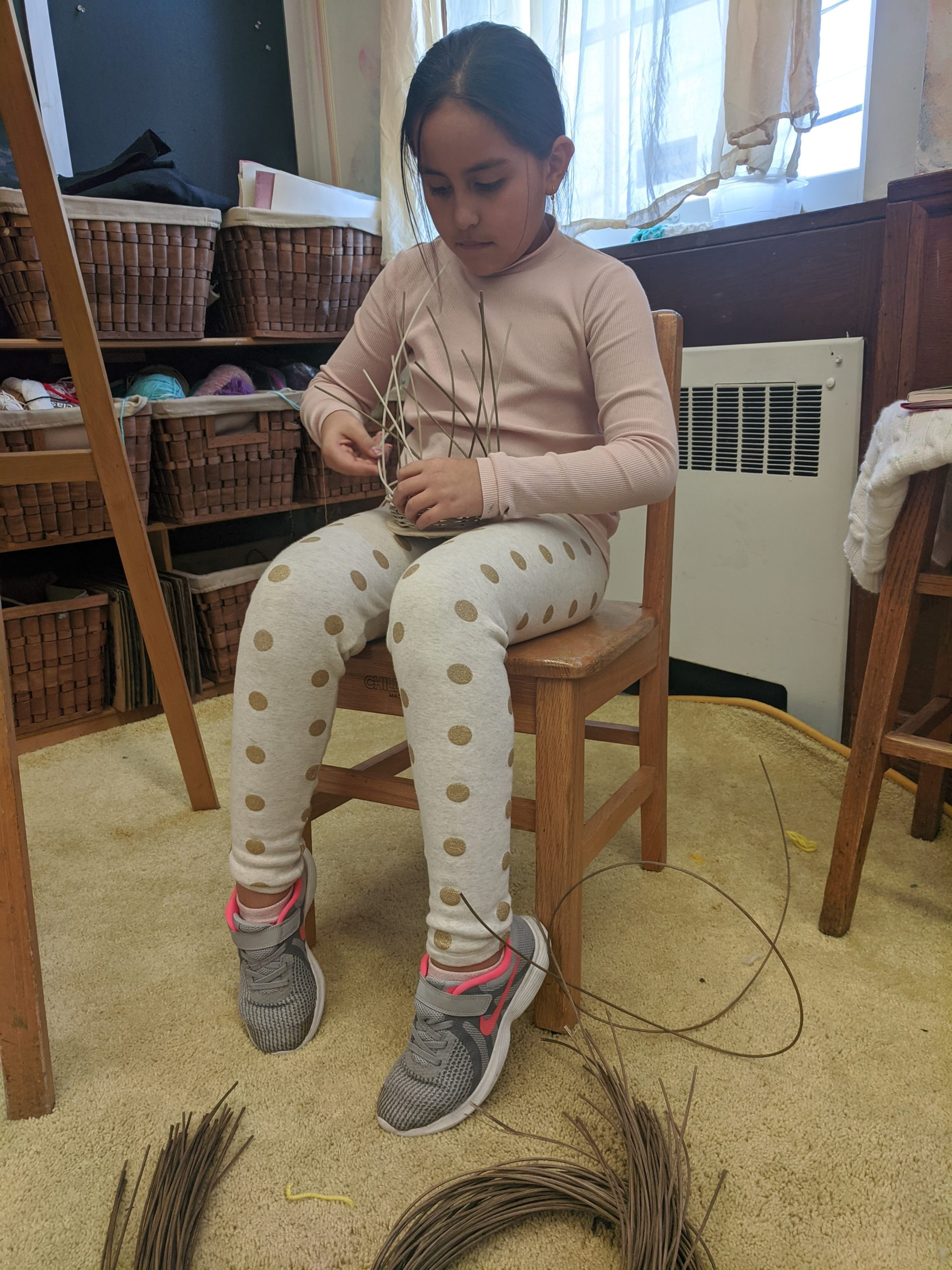 Sag Harbor Elementary School fourth-grader Samantha Garnica works a basket that is now a part of the school's display at the Student Arts Festival at Guild Hall.