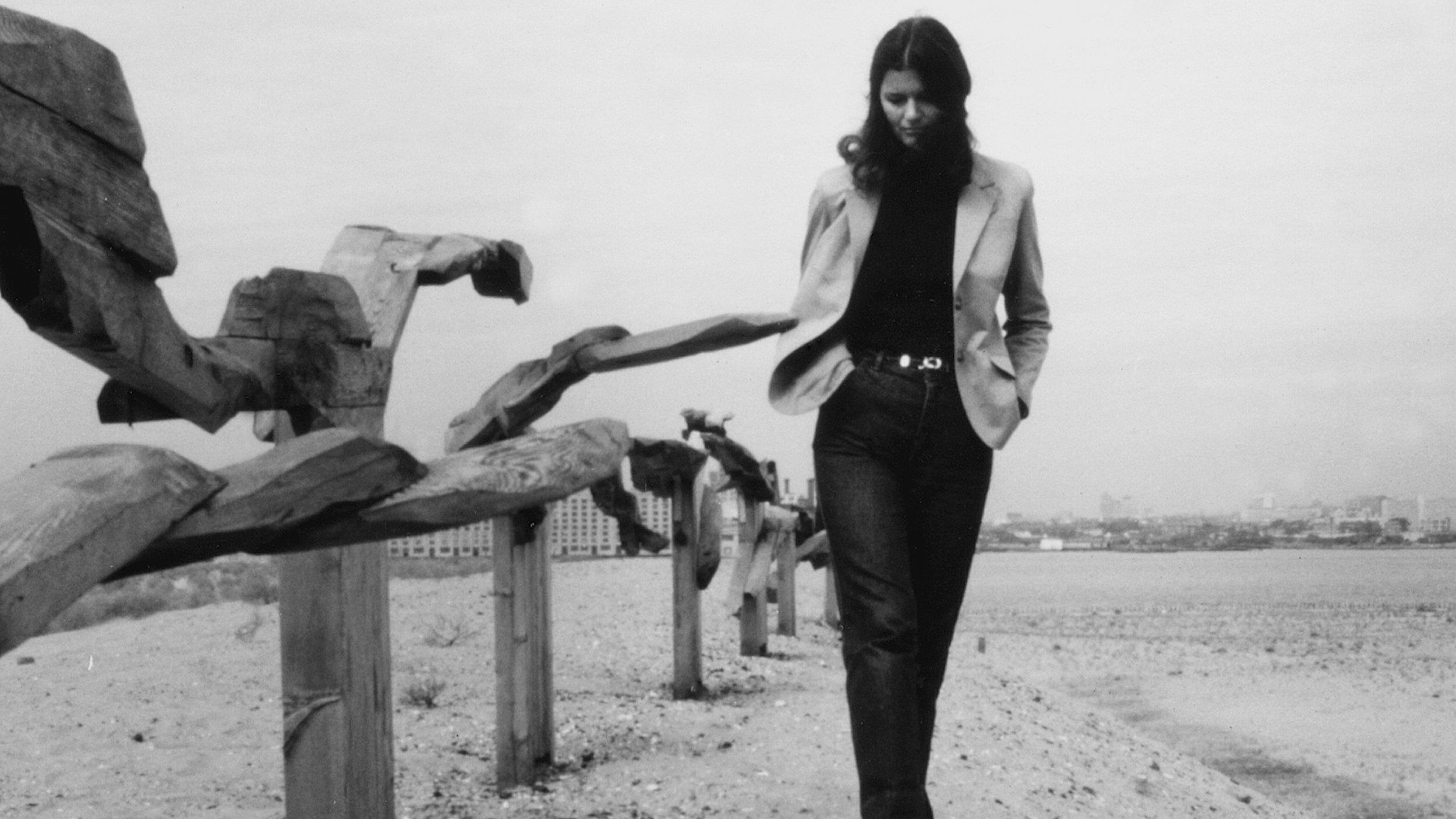"""Film still from """"Ursula von Rydingsvard: Into Her Own."""" Von Rydingsvard walking beside her work"""