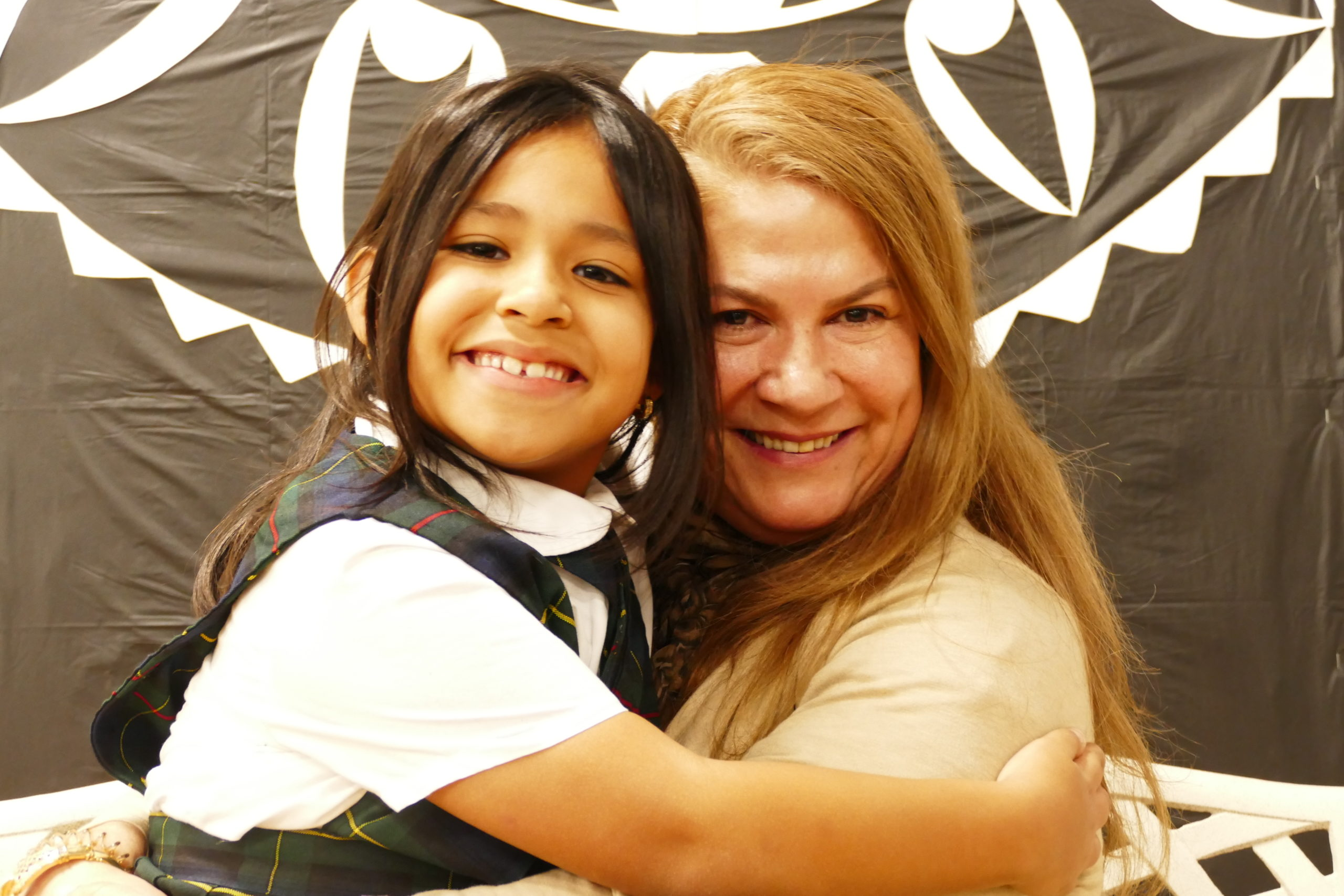 Our Lady of the Hamptons School second-grader Giressy Blandon hugs her grandmother, Blanca Correal during the school's recent celebration of Catholic Schools Week.