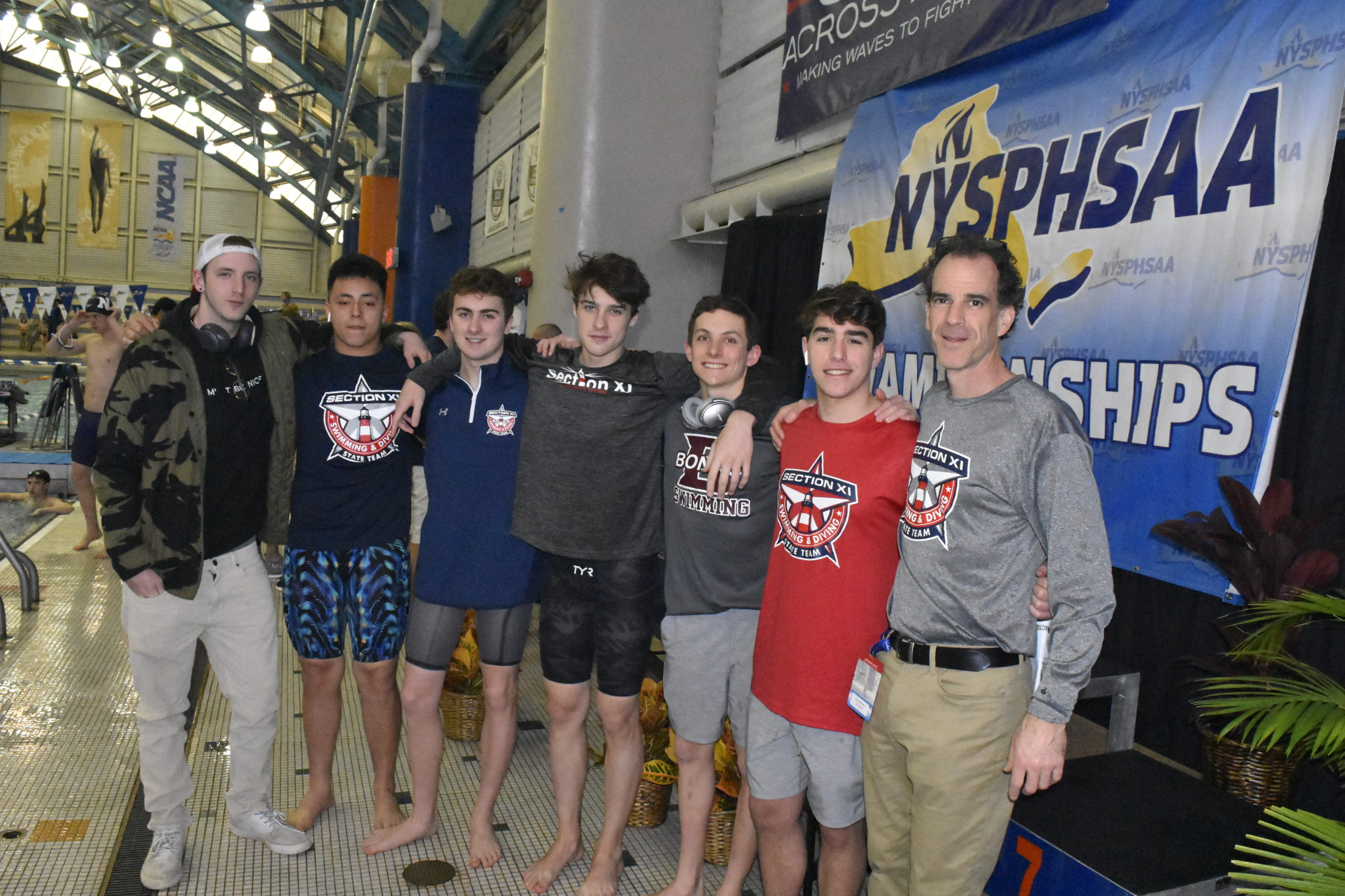 Bonackers, from left to right, Christian Gaines, Fernando Menjura, Owen McCormac, Colin Harrison, Jack Duryea, Aidan Forst and head coach Craig Brierley at the New York State Swimming Championships on Friday.  DREW BUDD