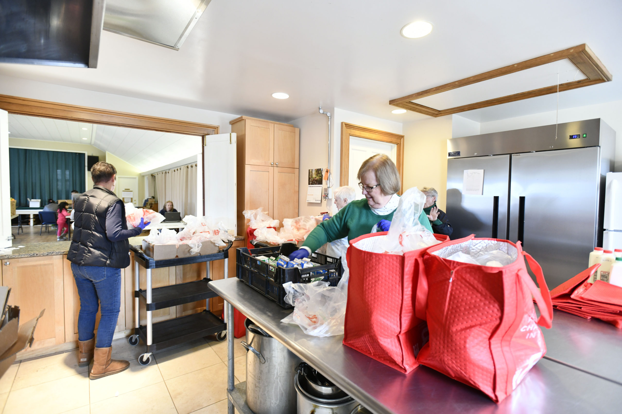 Linda Maconochie, Holly Wheaton and Deanna Tikkanen pack and distribute bags of food at the Springs Food Panrty on Wednesday, March 18.  DANA SHAW