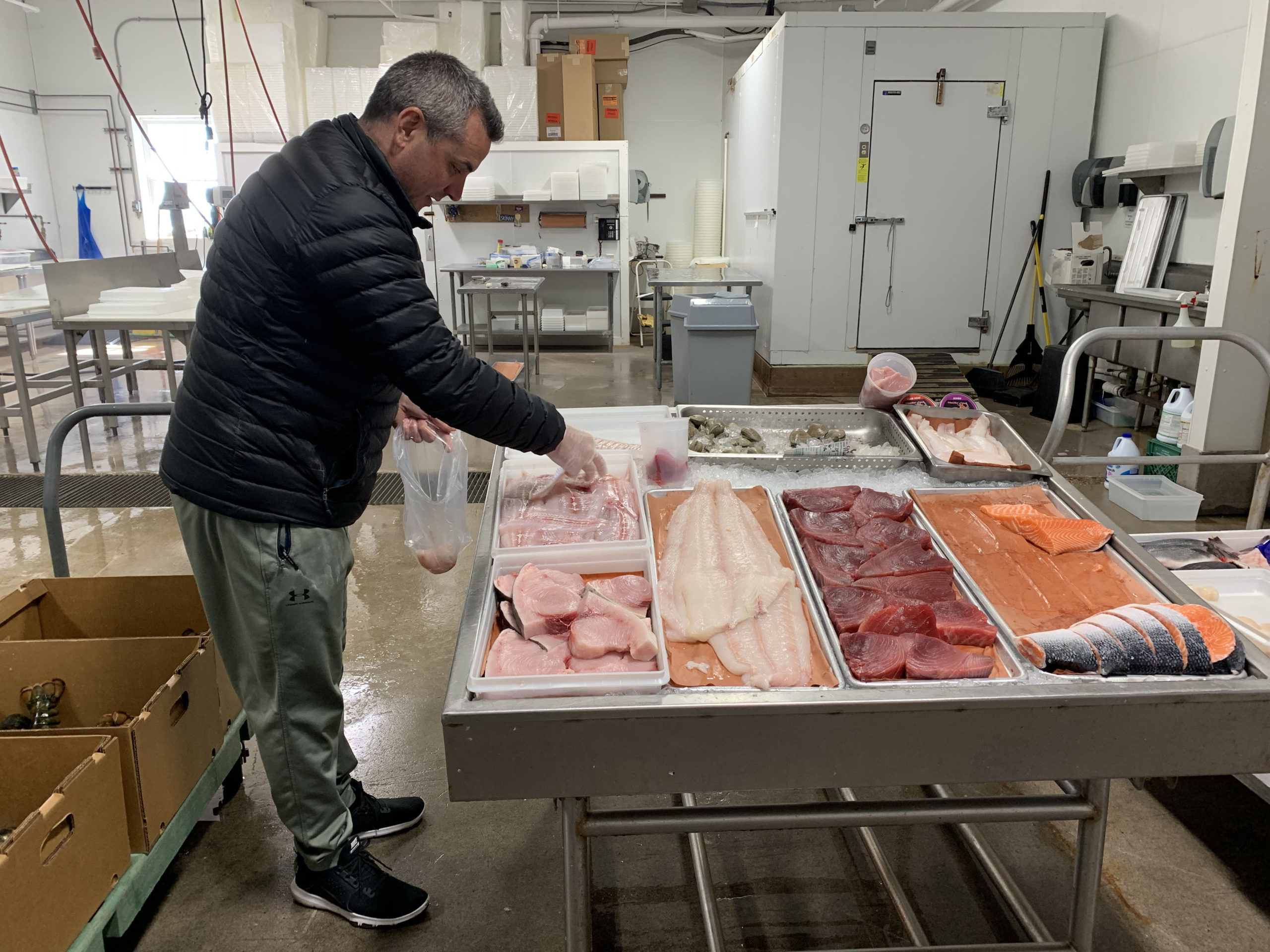 Asa Gosman serves customers form a makeshift retail seafood stand at Gosman's Fish Market in Montauk on Sunday.    GAVIN MENU