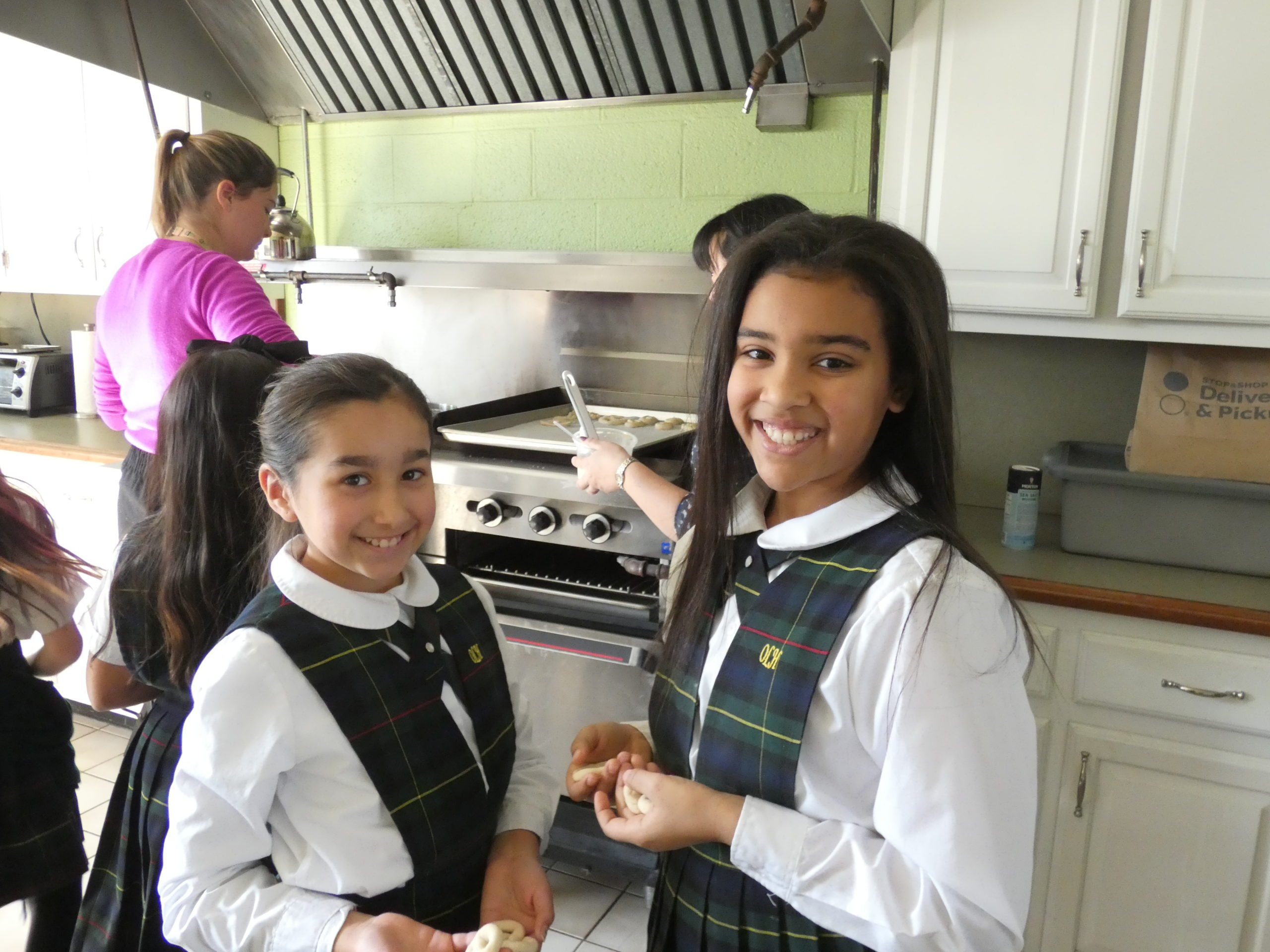 Our Lady of the Hamptons School fourth graders Tsanna Gierra and Aliah Donohoe work on a Lenten pretzel project.