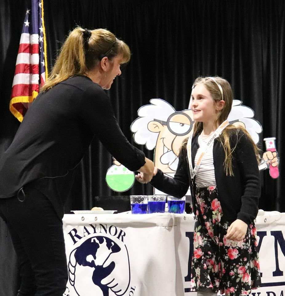 Raynor Country Day School third-grader Lilyanna Webste, recieves her medal from science teacher Elaine Marshall at Raynor Country Day School's recent Science Fair.