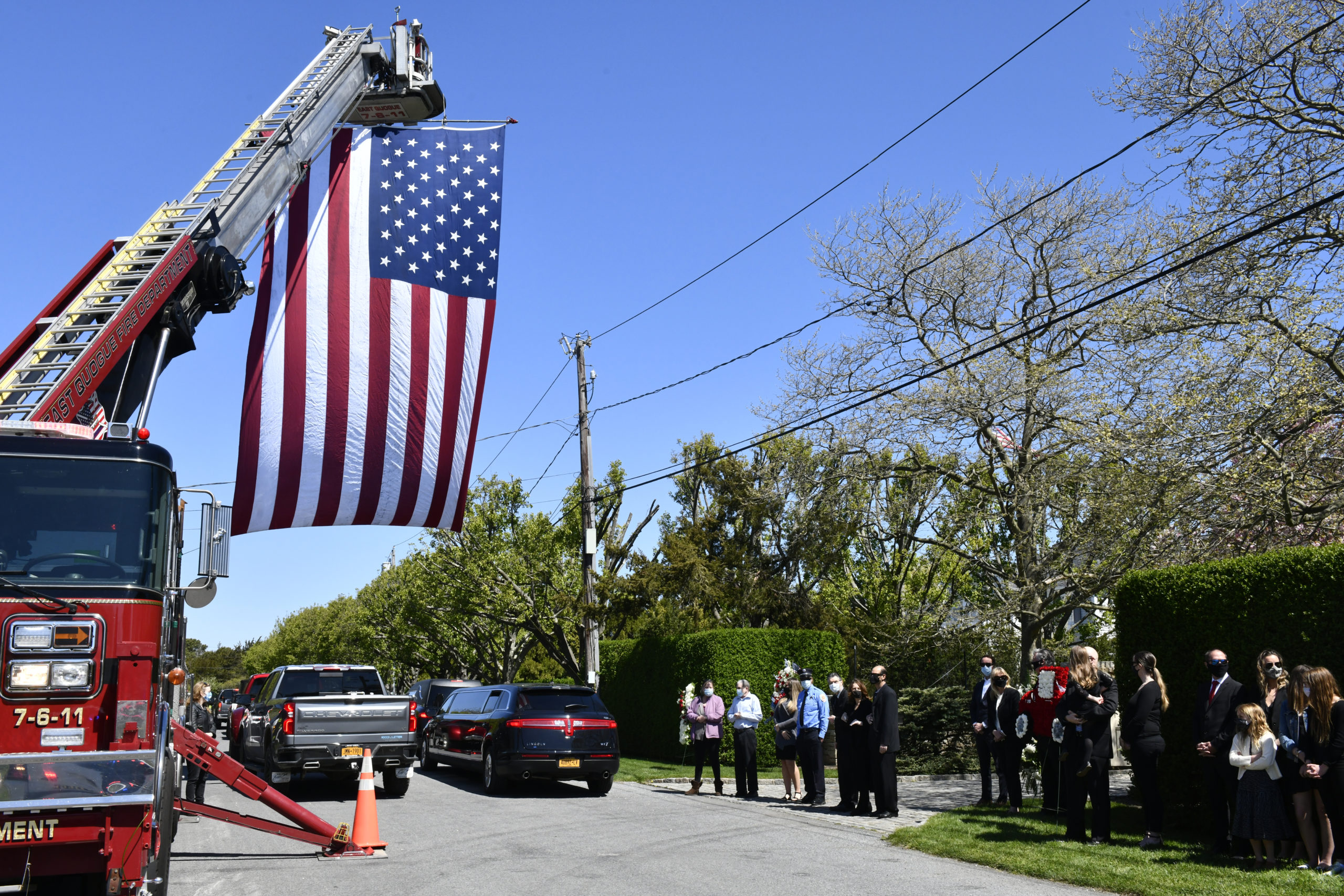 Members of the Quogue Fire Department line street heading to the home of George Mathys on May 13.  DANA SHAW