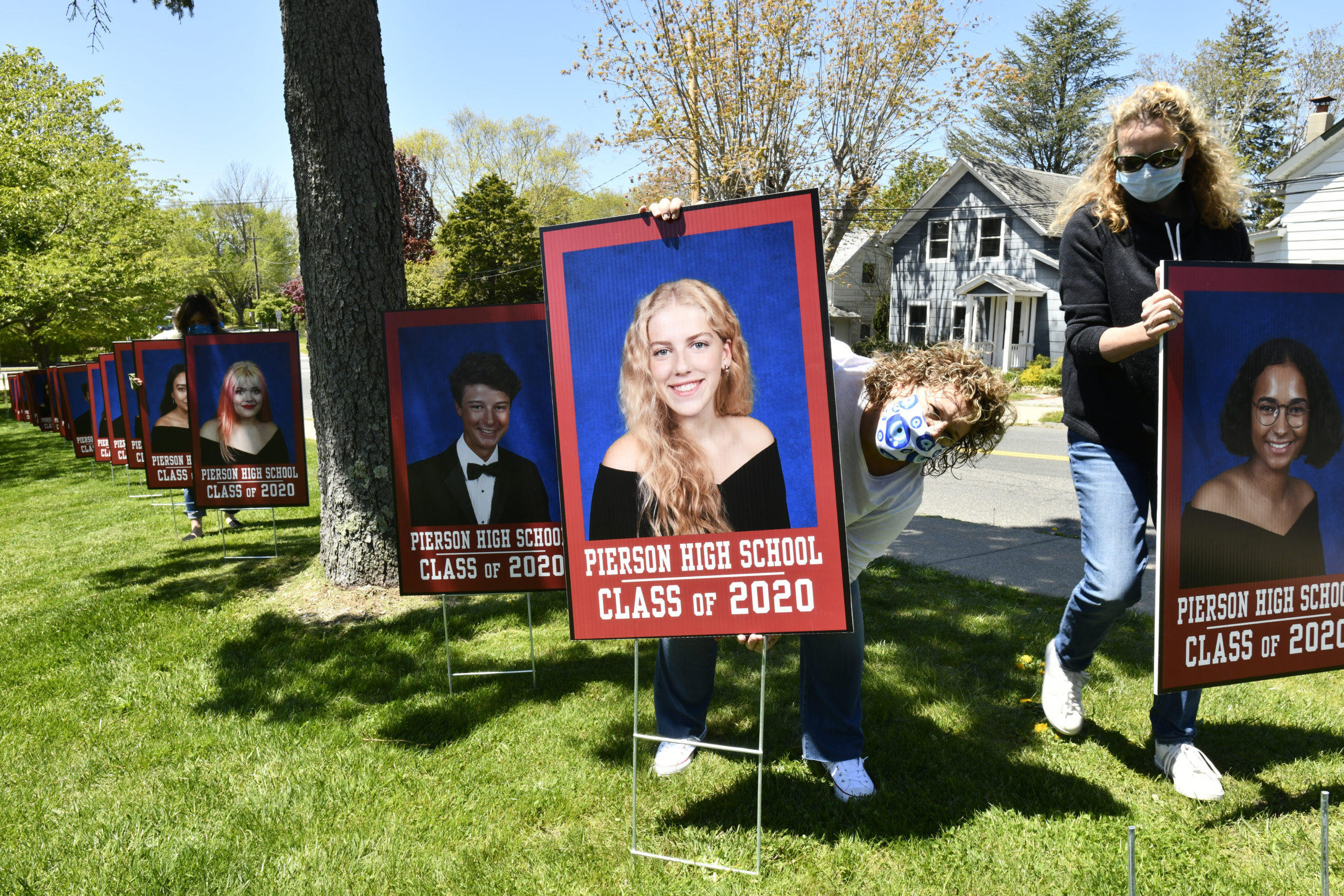 Stephanie Bitis and Pia Ferraris place photos of graduates on Pierson Hill on Wednesday.