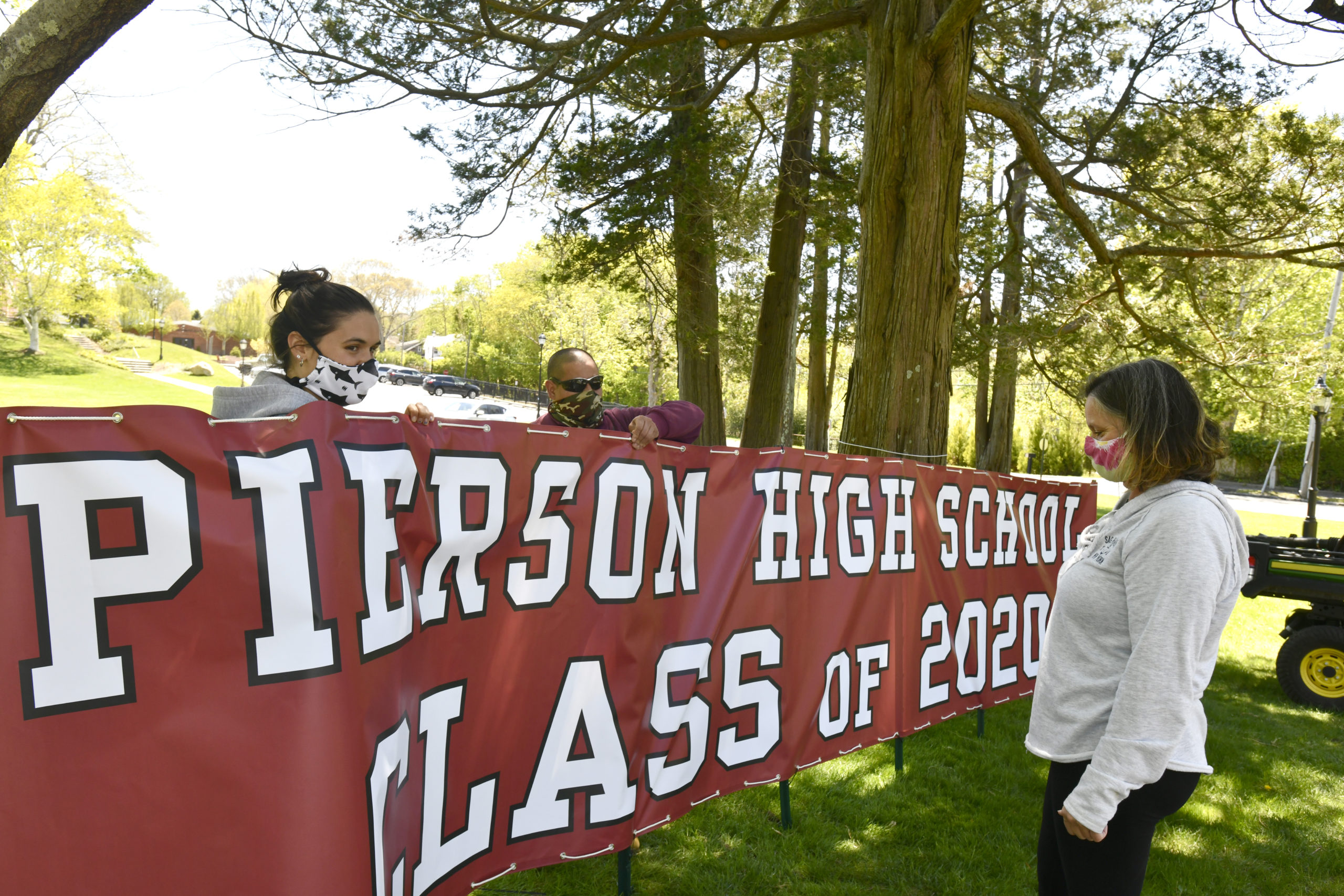 Emiley Nill, Jorge L. Maya and Fran Nill put up the sign at Pierson High School on Wednesday.