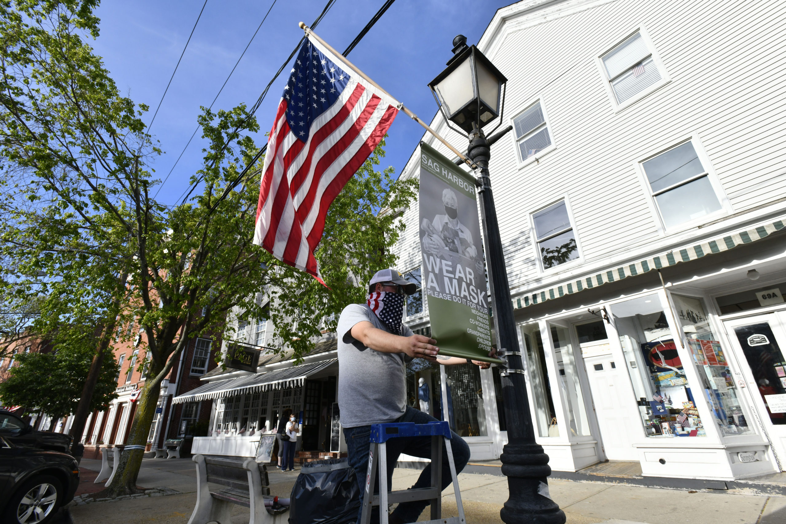 Will McLear of Ocean Graphics installs banners in on Main Street in Sag Harbor on Friday evening as part of