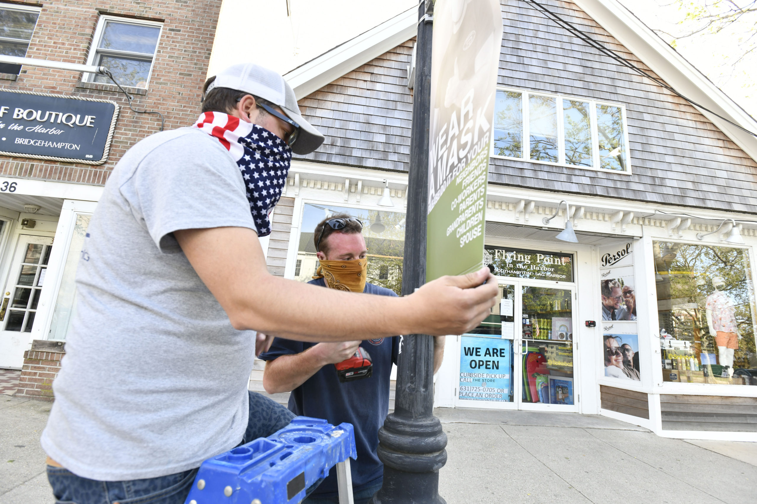 Will McLear and Frank Bernzott install banners in on Main Street in Sag Harbor on Friday evening as part of