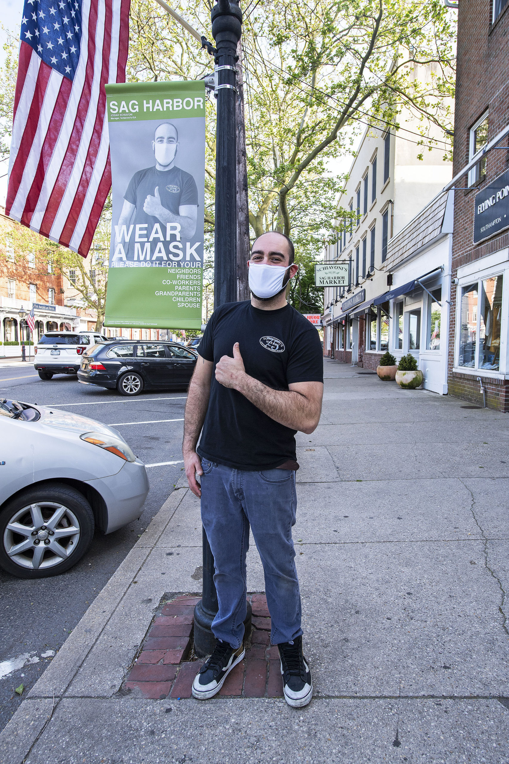Josiah Schiavoni in front of the banner on Main Street he posed for as part of the Sag Harbor Wear A Mask campaign, photographed on Friday.  MICHAEL HELLER