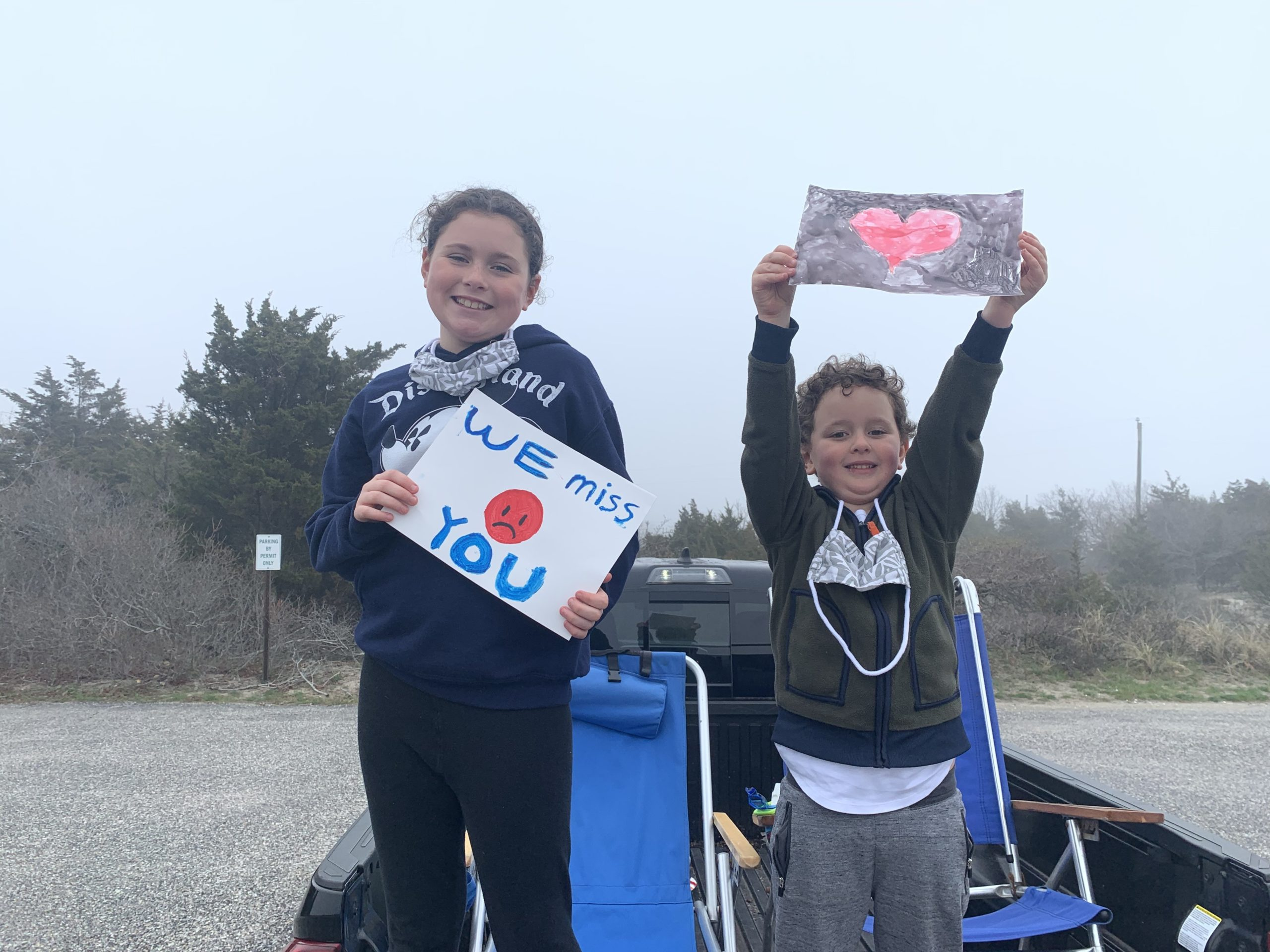 Ella and Charlie Menu display signs for their teachers during a Springs School Spirit Team drive on Friday morning that had teachers and administrators driving throughout the hamlet to let students know they were thinking about them.