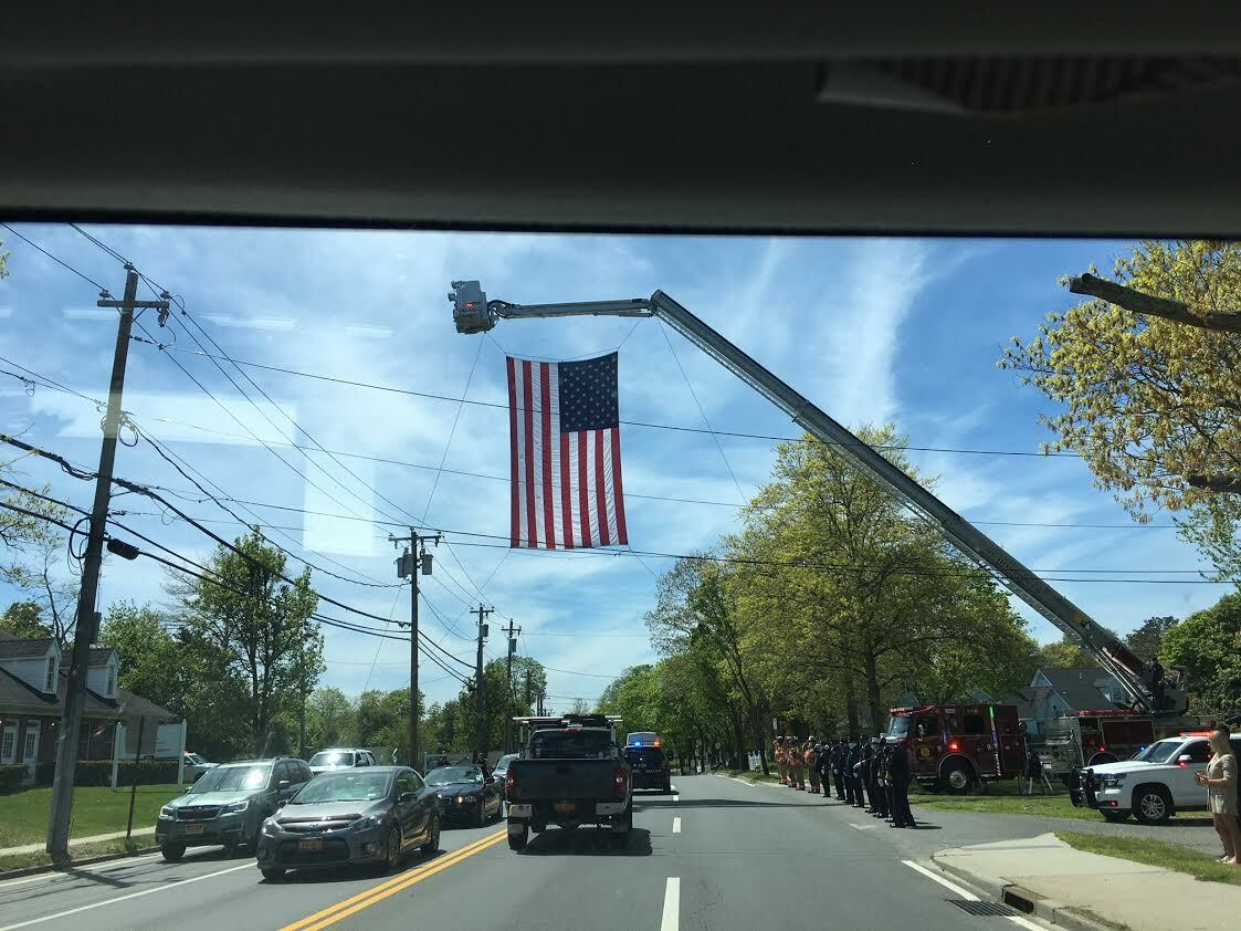 Cranes hoistd flags over Montauk Highway along the funeral procession route. LORI SIDOR