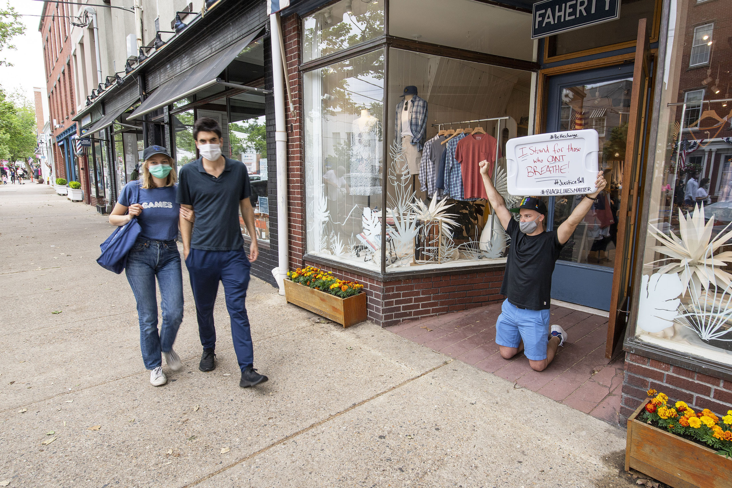 Unable to leave work, Jeremy Impelliveri makes his voice heard from the doorway of the Faherty store as marchers make their way down Main Street during a Black Lives Matter protest rally held in Steinbeck Park on Friday afternoon.    MICHAEL HELLER