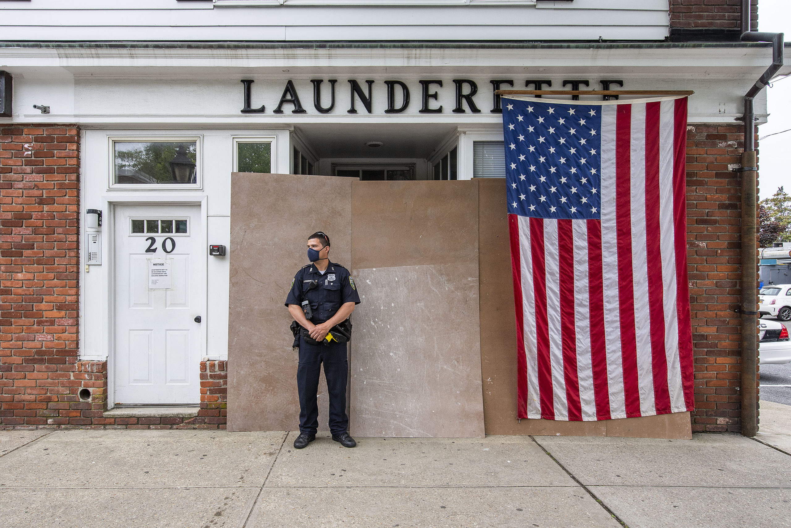 Riverhead Police Officer Patrick Loszweski watches marchers make their way down Main Street from in front of the hastily-barricaded Sag Harbor Launderette during a Black Lives Matter protest rally held in Steinbeck Park on Friday afternoon.   MICHAEL HELLER