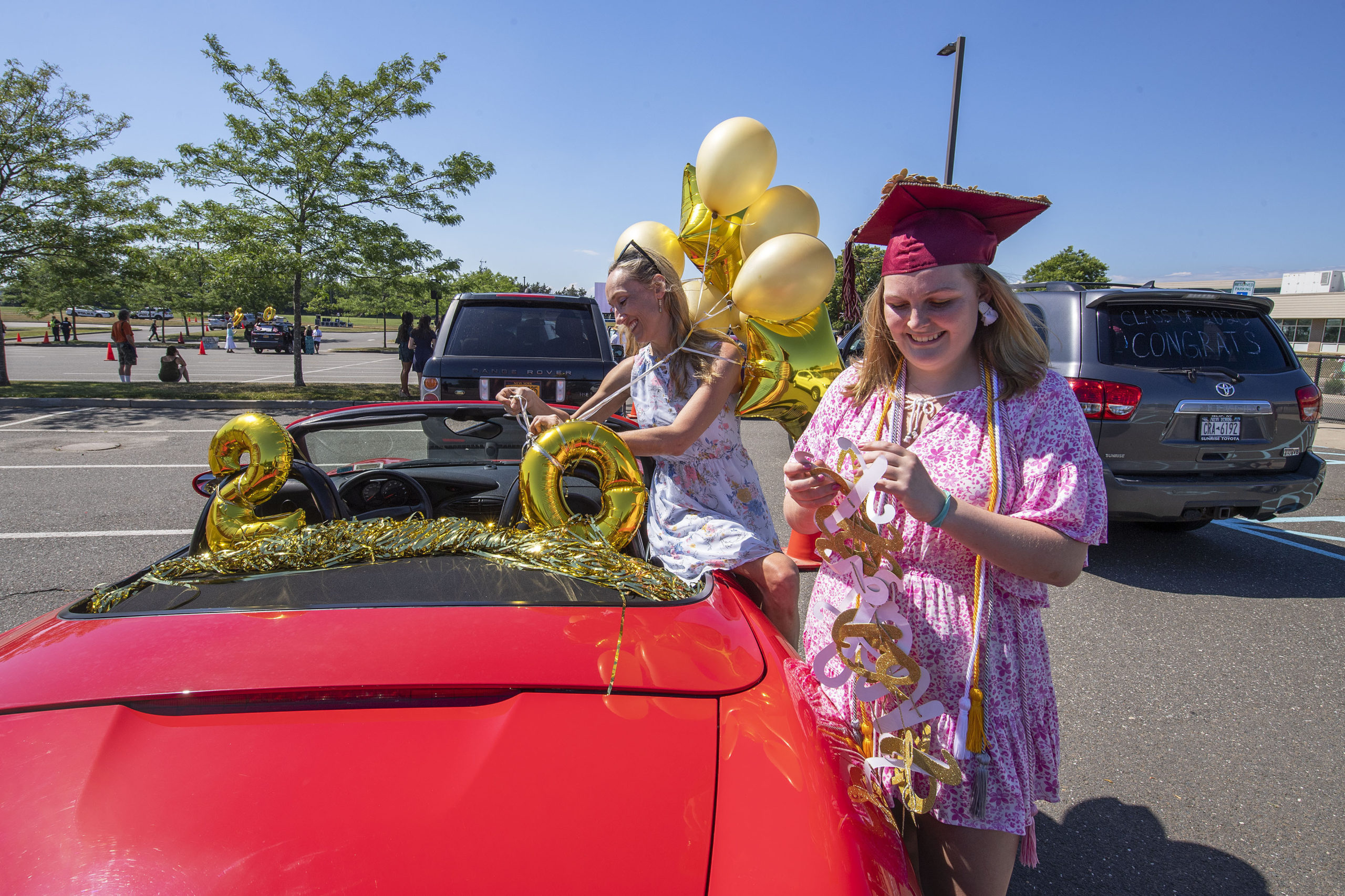 East Hampton High School Senior Remy Campbell helps her mom Aimee add decorations to her family's car as she gets ready to participate in the 2020 graduation ceremony at the East Hampton High School on Friday.