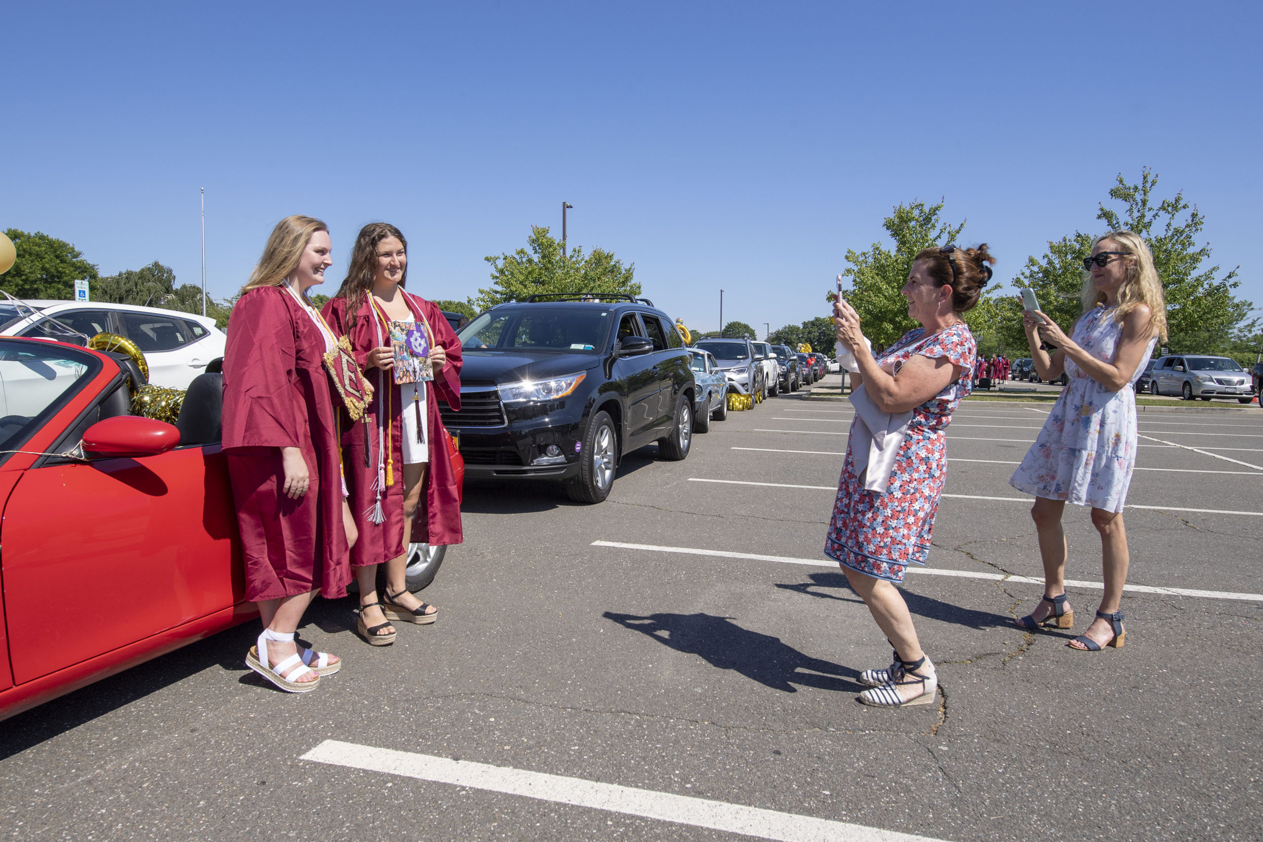 East Hampton High School Seniors Remy Campbell and Kelly Seitz get their photo taken by mom Anne Marie Seitz as they get ready to participate in the 2020 graduation ceremony at the East Hampton High School on Friday.