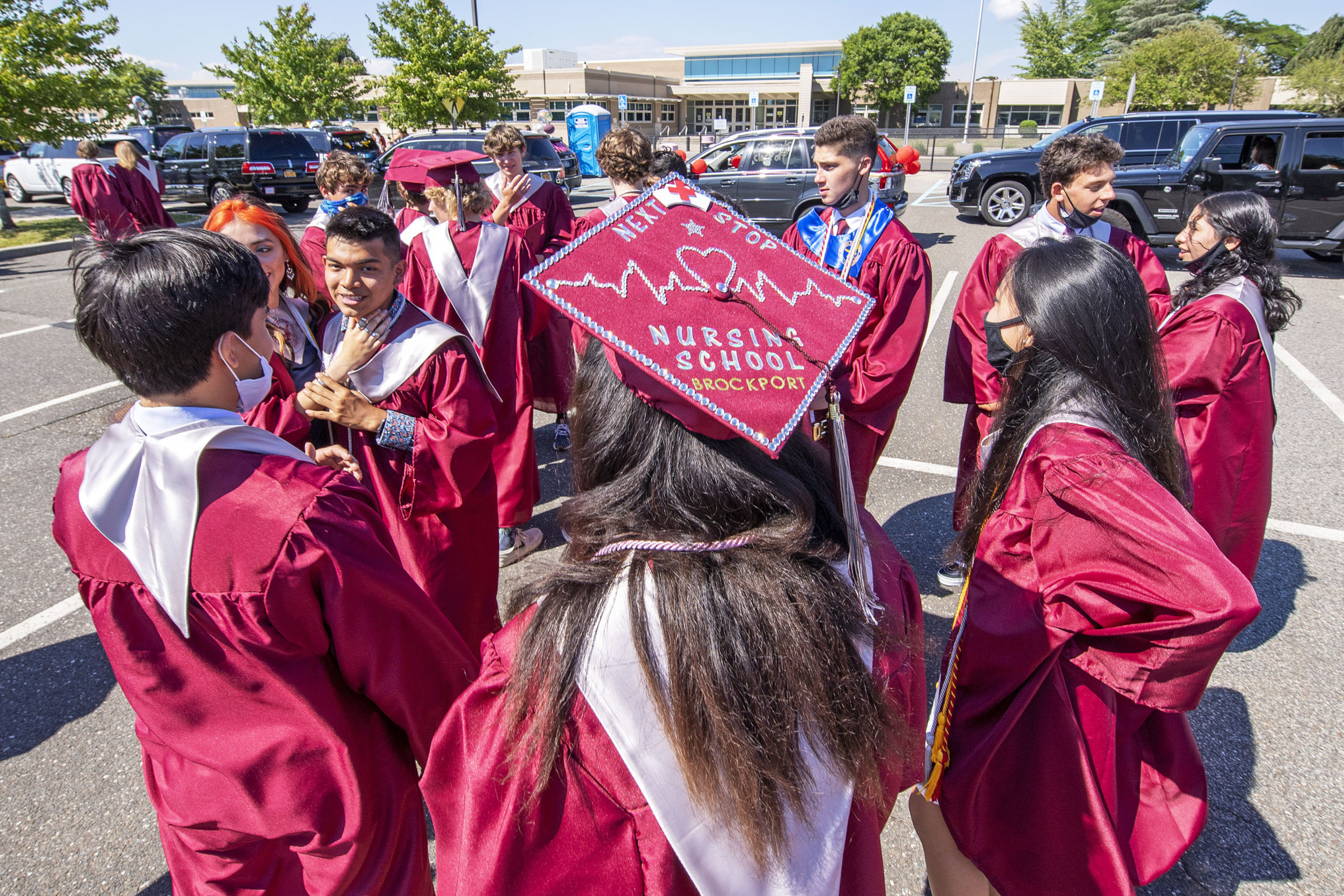 East Hampton High School Senior Tia Weiss proudly shows off her next stop as she greets her classmates in the parking lot as she gets ready to participate in the 2020 graduation ceremony at the East Hampton High School on Friday.