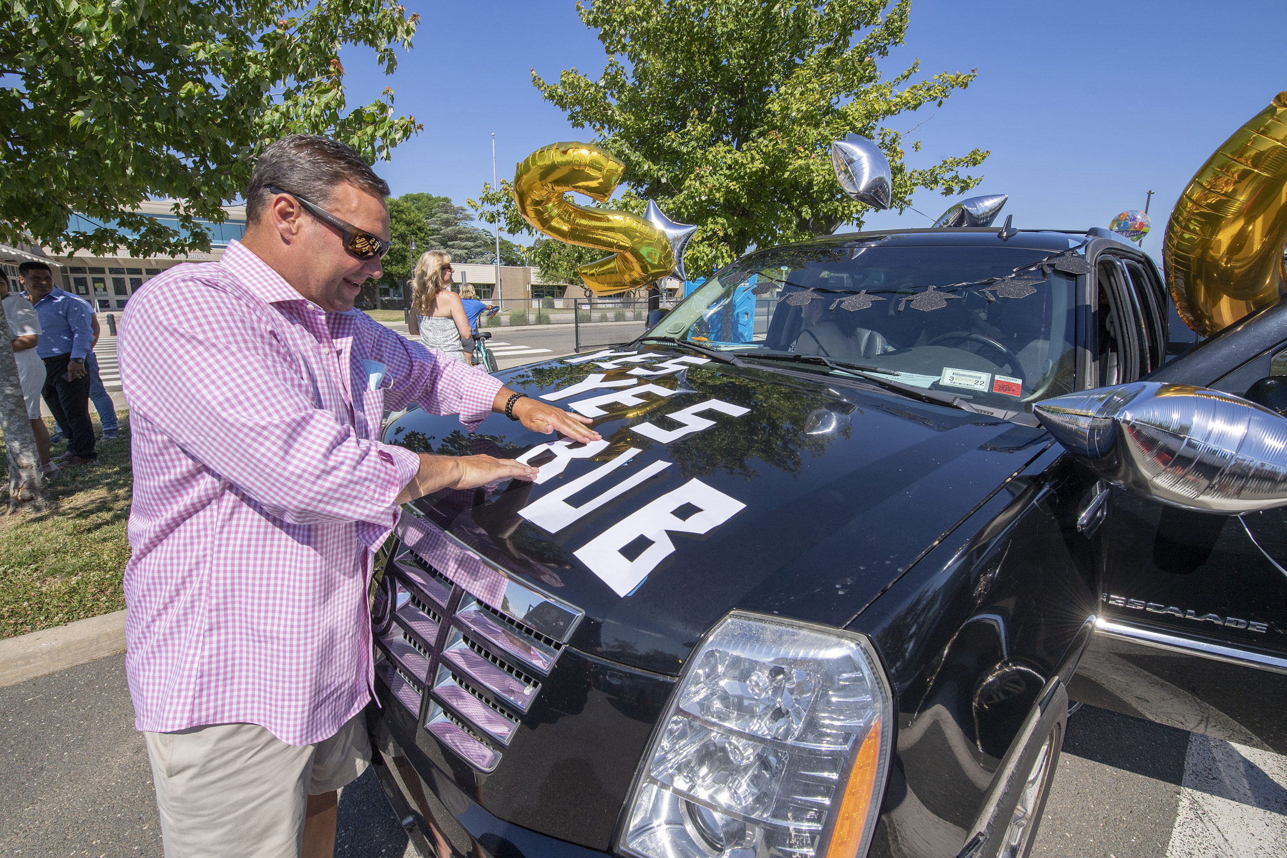 Brian Villante shows some Bonac pride as he decorates his car in the parking lot prior to the 2020 graduation ceremony at the East Hampton High School on Friday.