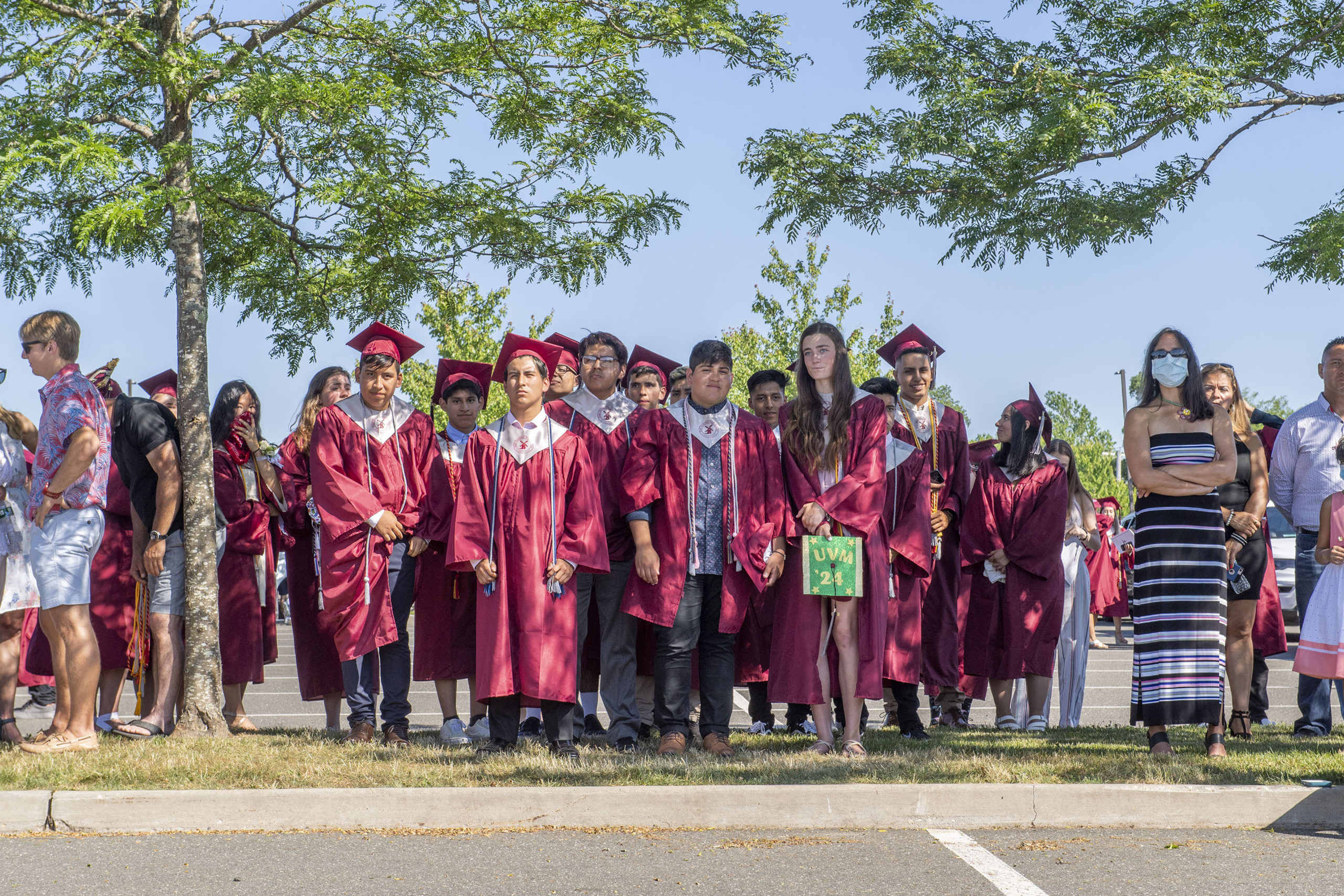 Seniors and their families watched the ceremony from the shade of some trees in the parking lot during the 2020 graduation ceremony at the East Hampton High School on Friday.
