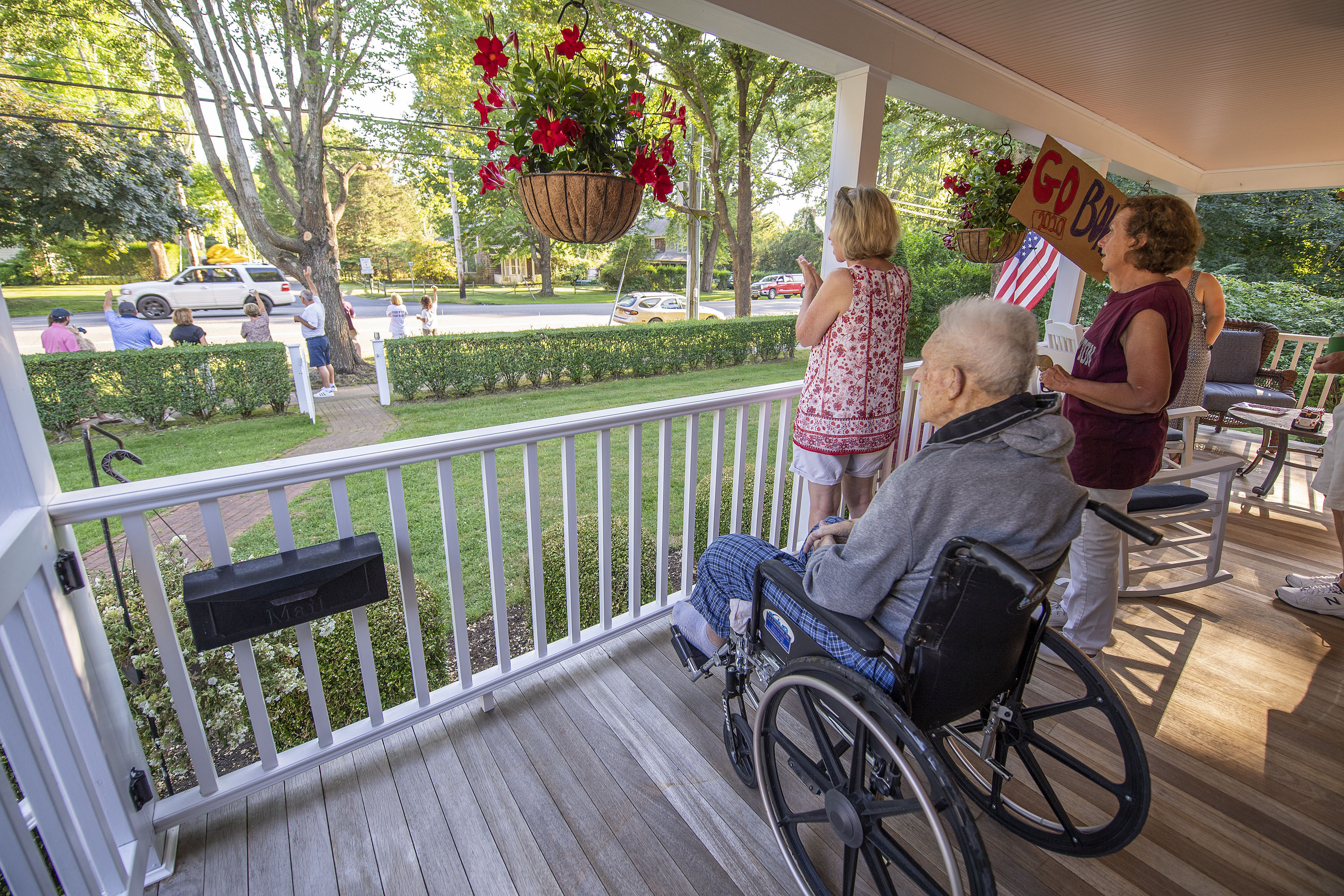 Eighty- three-year-old John McGuirk, Sr. watches the parade of passing East Hampton High School graduates from his front porch on Newtown Lane following the 2020 graduation ceremony at the East Hampton High School on Friday.
