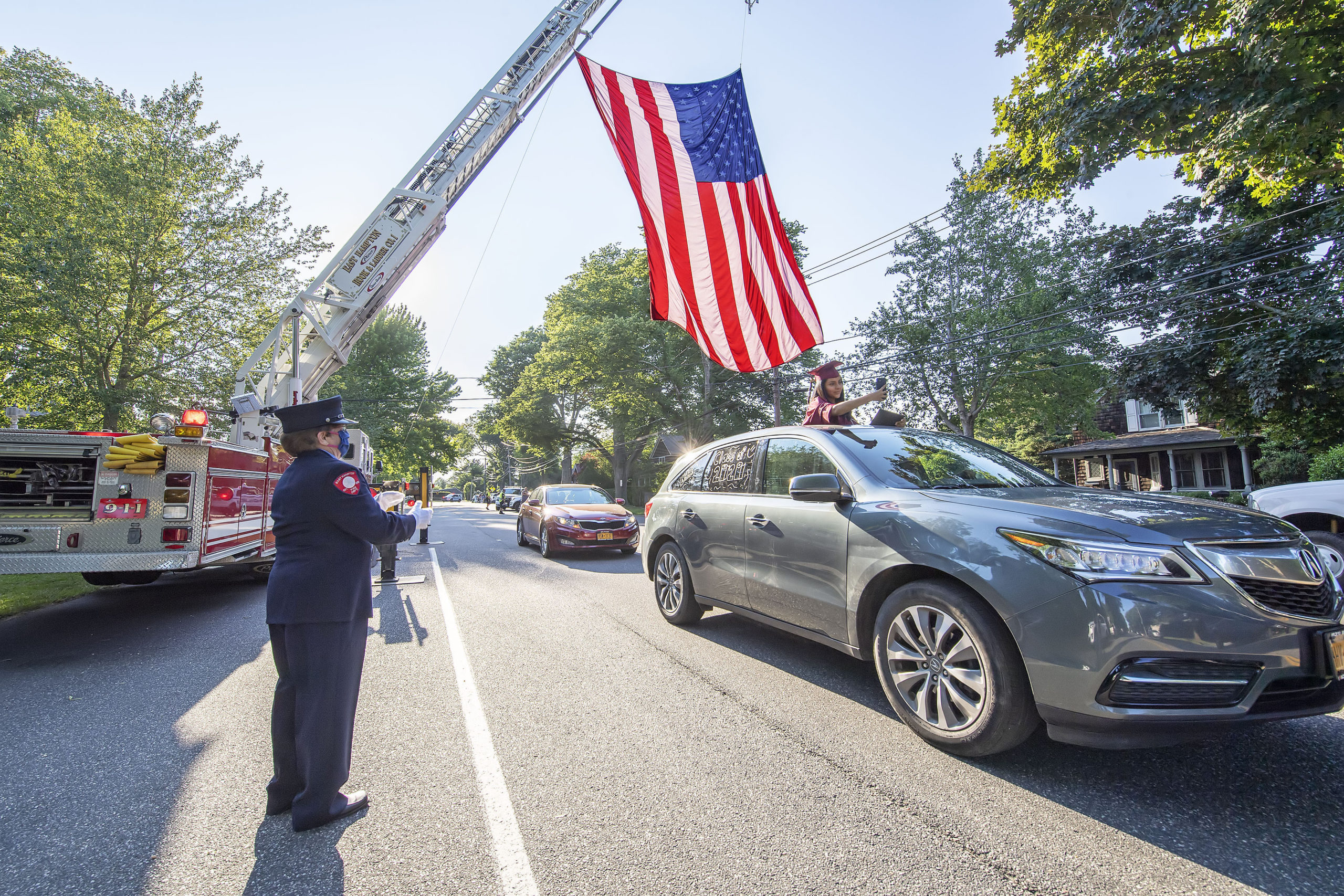 A newly-graduated East Hampton High School senior gets a round of applause from East Hampton Fire Department Fire Police member Joan Jacobs as she photographs herself passing underneath a large American flag hoisted by EHFD Hool & Ladder Co.#1 in honor on the graduates on Newtown Lane following the 2020 graduation ceremony at the East Hampton High School on Friday.