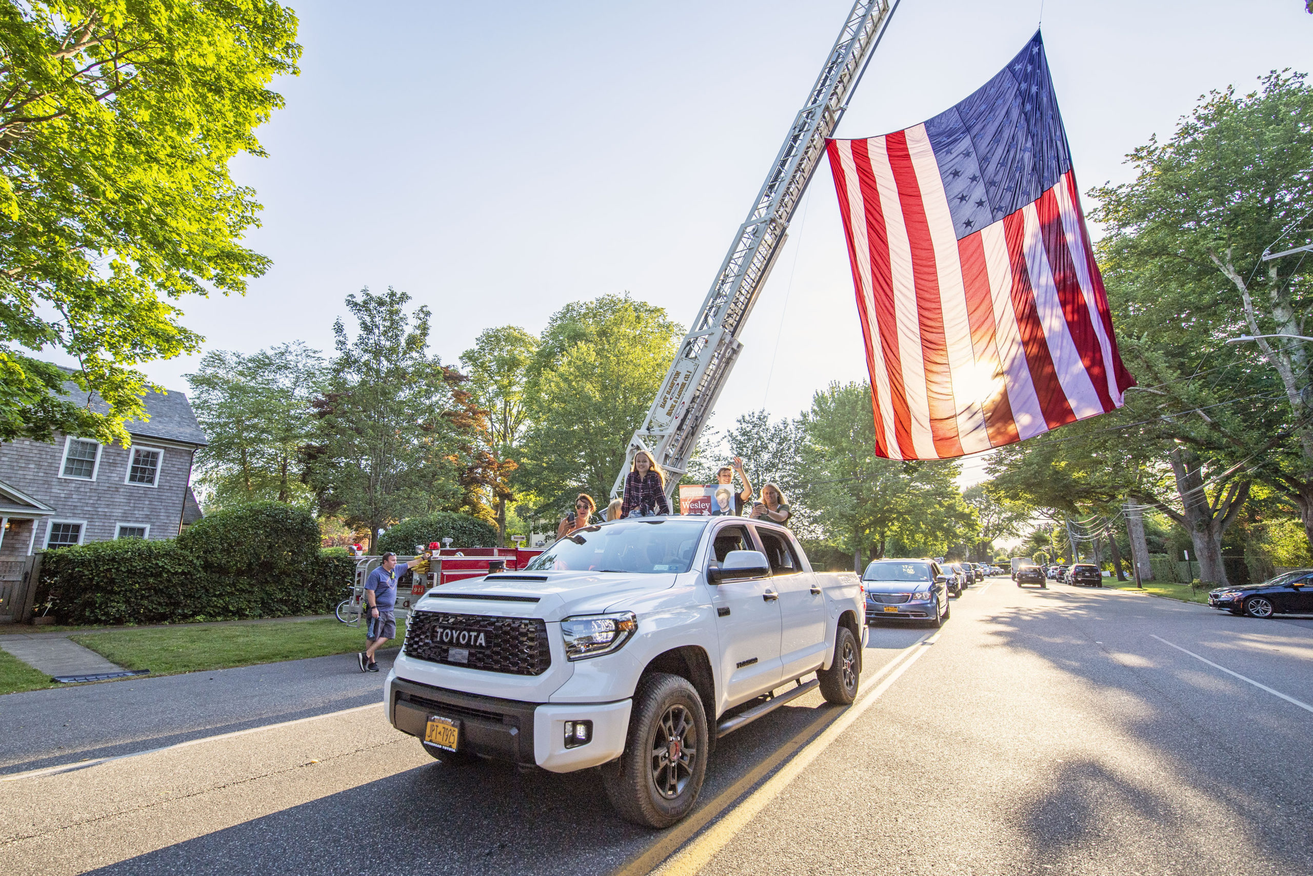 A newly-graduated East Hampton High School senior pass underneath a large American flag hoisted by EHFD Hool & Ladder Co.#1 in honor on the graduates on Newtown Lane following the 2020 graduation ceremony at the East Hampton High School on Friday.