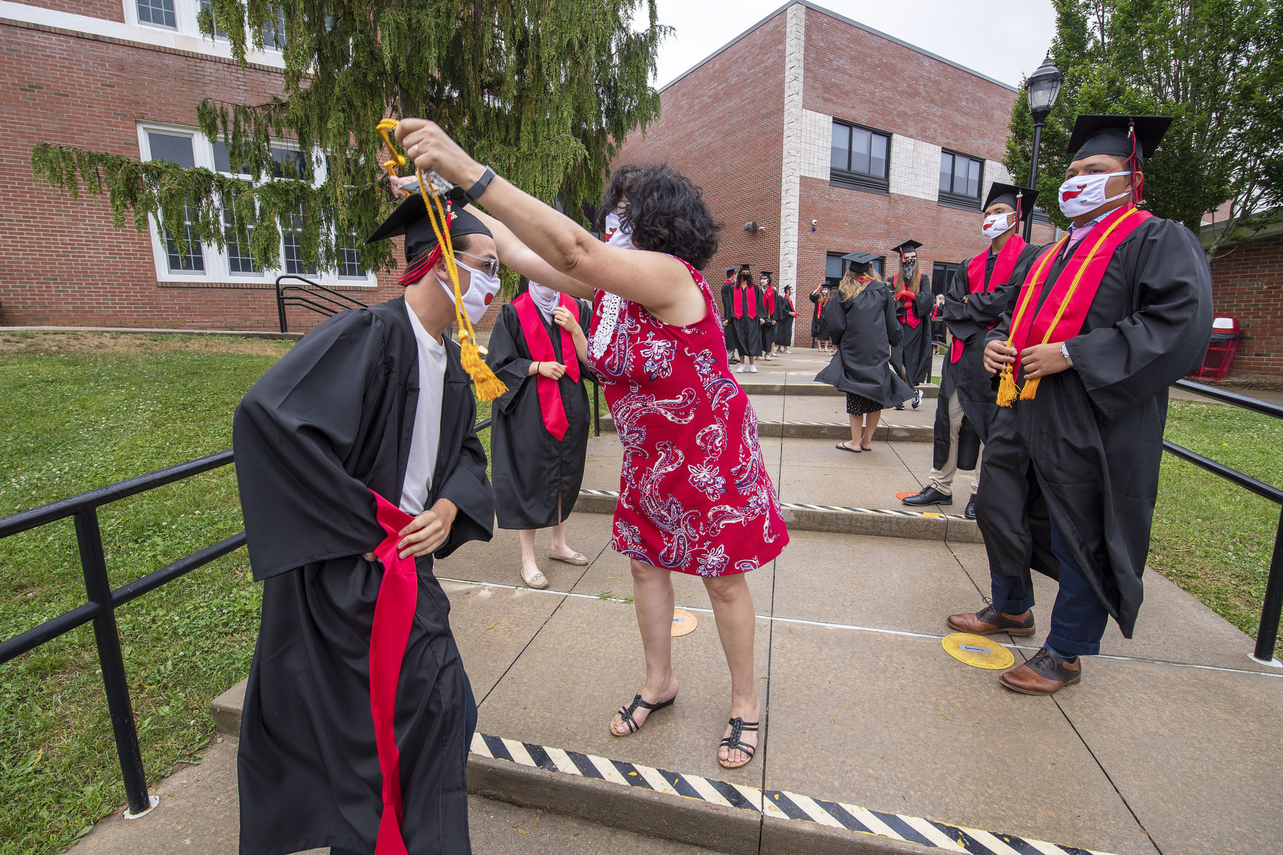 Yanni Bitis gets some help from Senior Class Advisor Terri Federico prior to the start of the Pierson High School 2020 Commencement Ceremony at Pierson High School on Saturday.