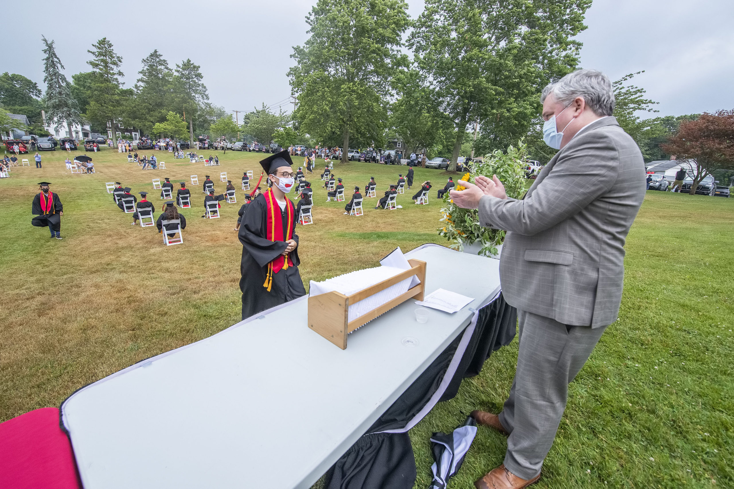 Pierson High School Assistant Principal Mike Guinan applauds Yanni Bitis as he steps up to take his diploma during the Pierson High School 2020 Commencement Ceremony at Pierson High School on Saturday.