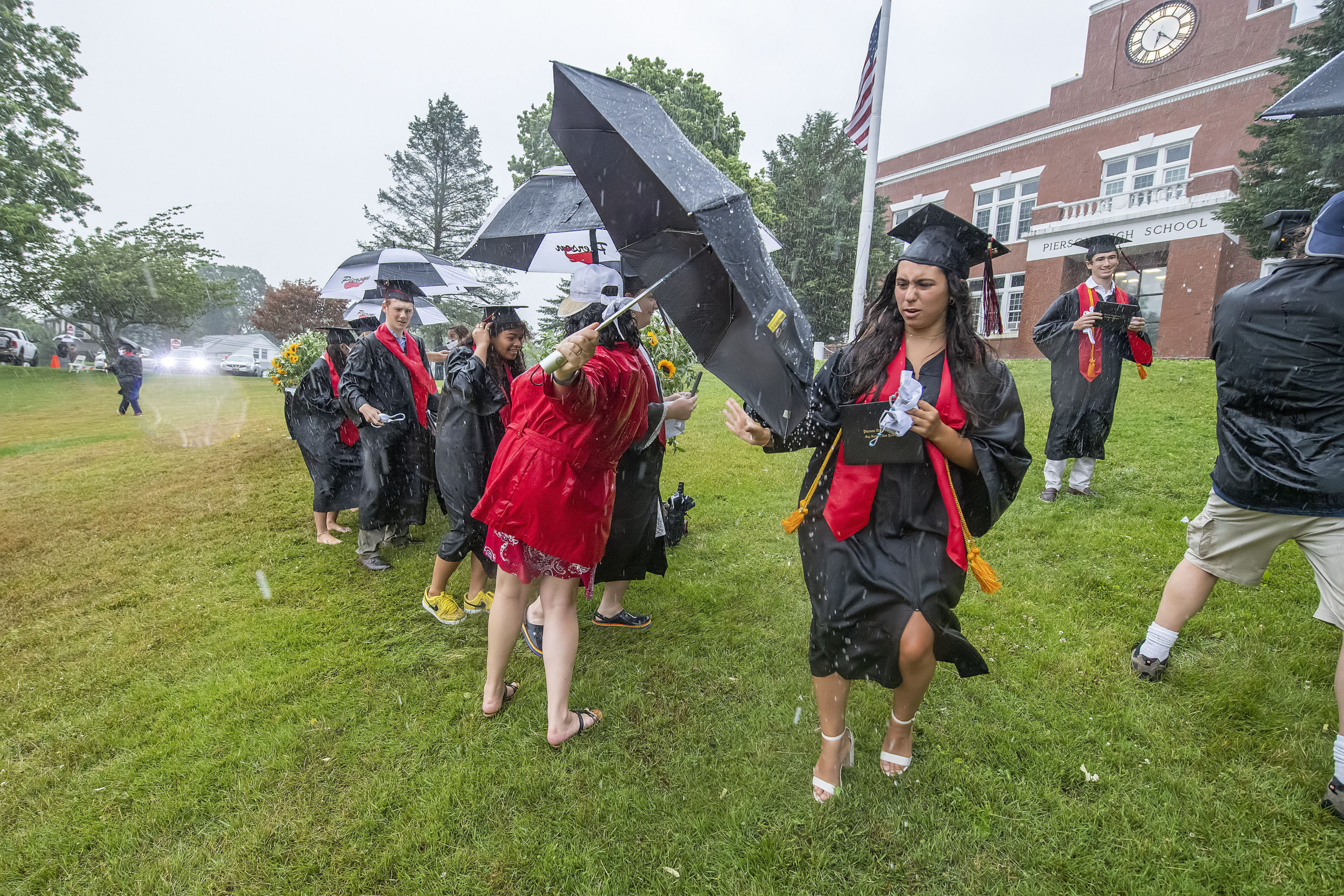 Senior Carly Gulotta rushes to get back to her seat after receiving her diploma and being photographed amidst the scramble in the pouring rain during the Pierson High School 2020 Commencement Ceremony at Pierson High School on Saturday.