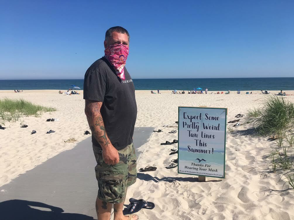 The sign tells visitors to expect weird tan lines this summer, as Westhampton Beach Village Board member Brian Tymann rocks his mask,