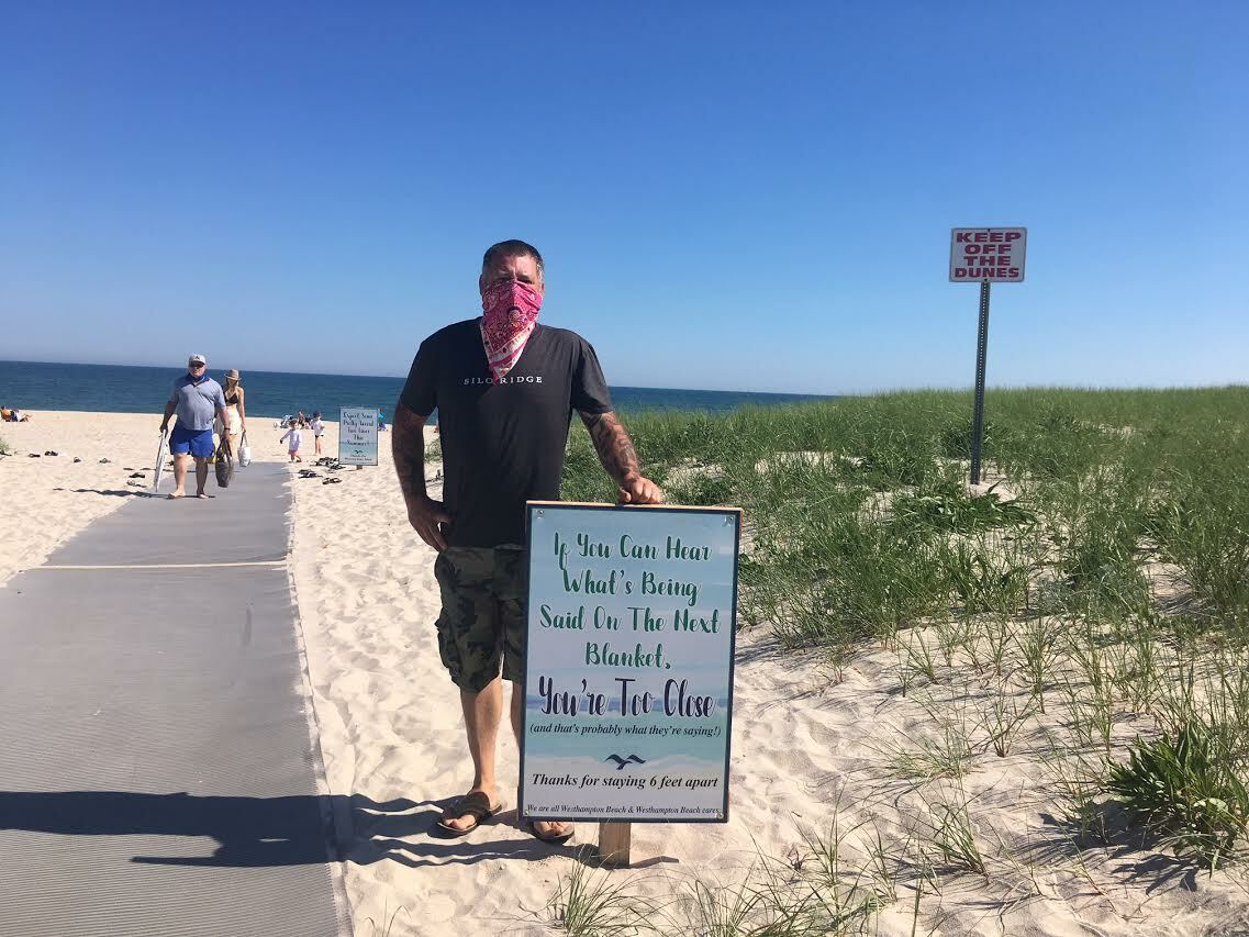 The sign warns visitors to maintain social distance. Westhampton Beach Village Board member Brian Tymann creidts colleague, Mayor Maria Moore, with coming up with the catchy verbiage.  KITTY MERRILL