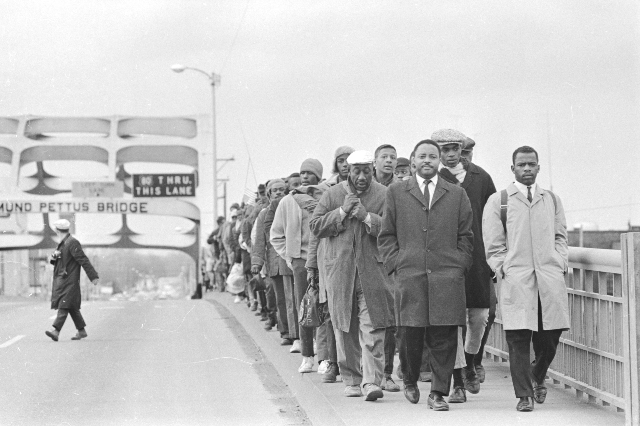 "John Lewis with fellow protesters at Edmund Pettus Bridge, in ""John Lewis: Good Trouble,"" a Magnolia Pictures release. © Alabama Department of Archives and History. Donated by Alabama Media Group. Photo by Tom Lankford, Birmingham News."