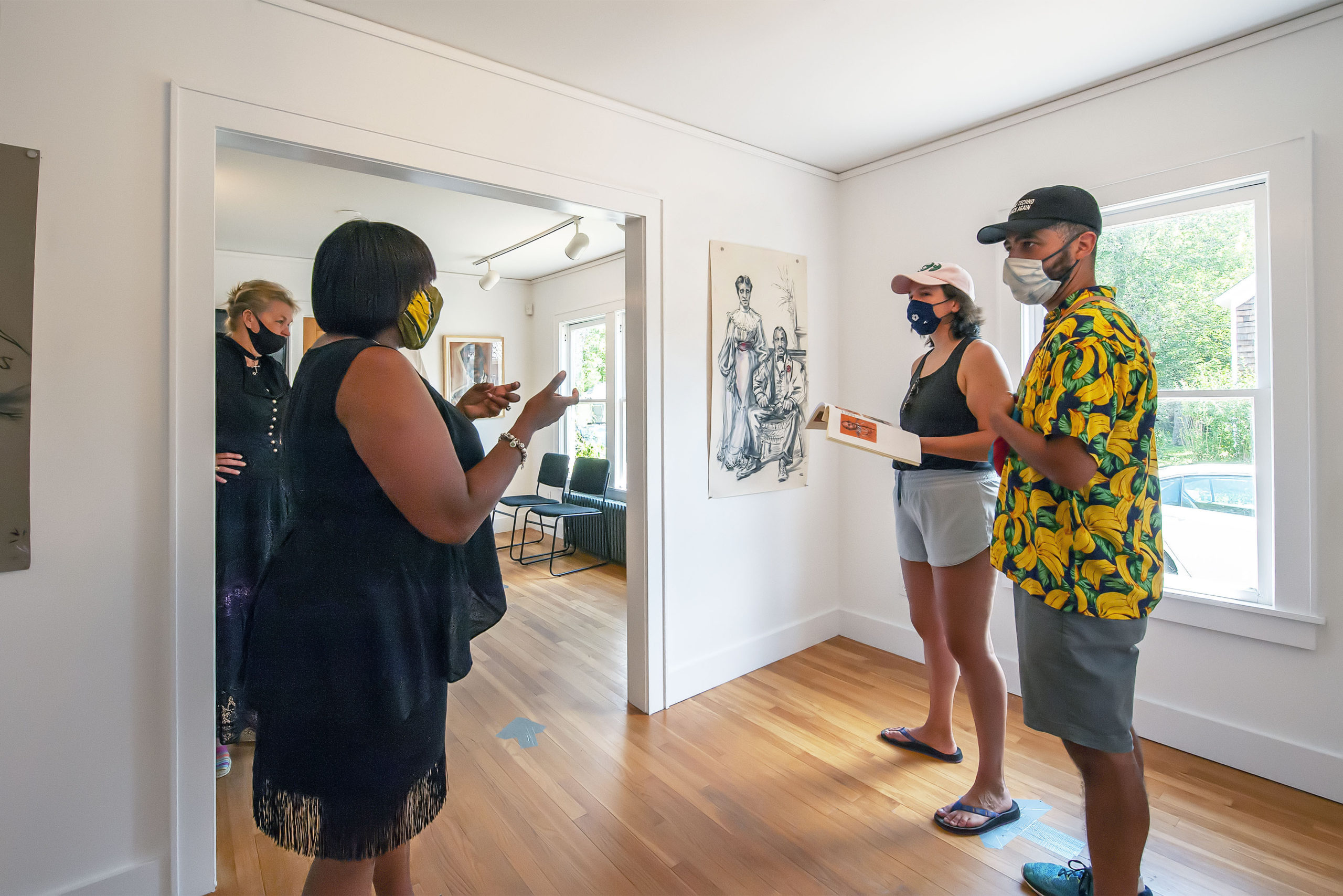 As artist Sabina Streeter looks on AS curator Dr. Georgette Grier of the Eastville Historical Society speaks about her artwork to visitors just prior to the opening of her exhibition at the Society's Heritage House on Saturday.   MICHAEL HELLER