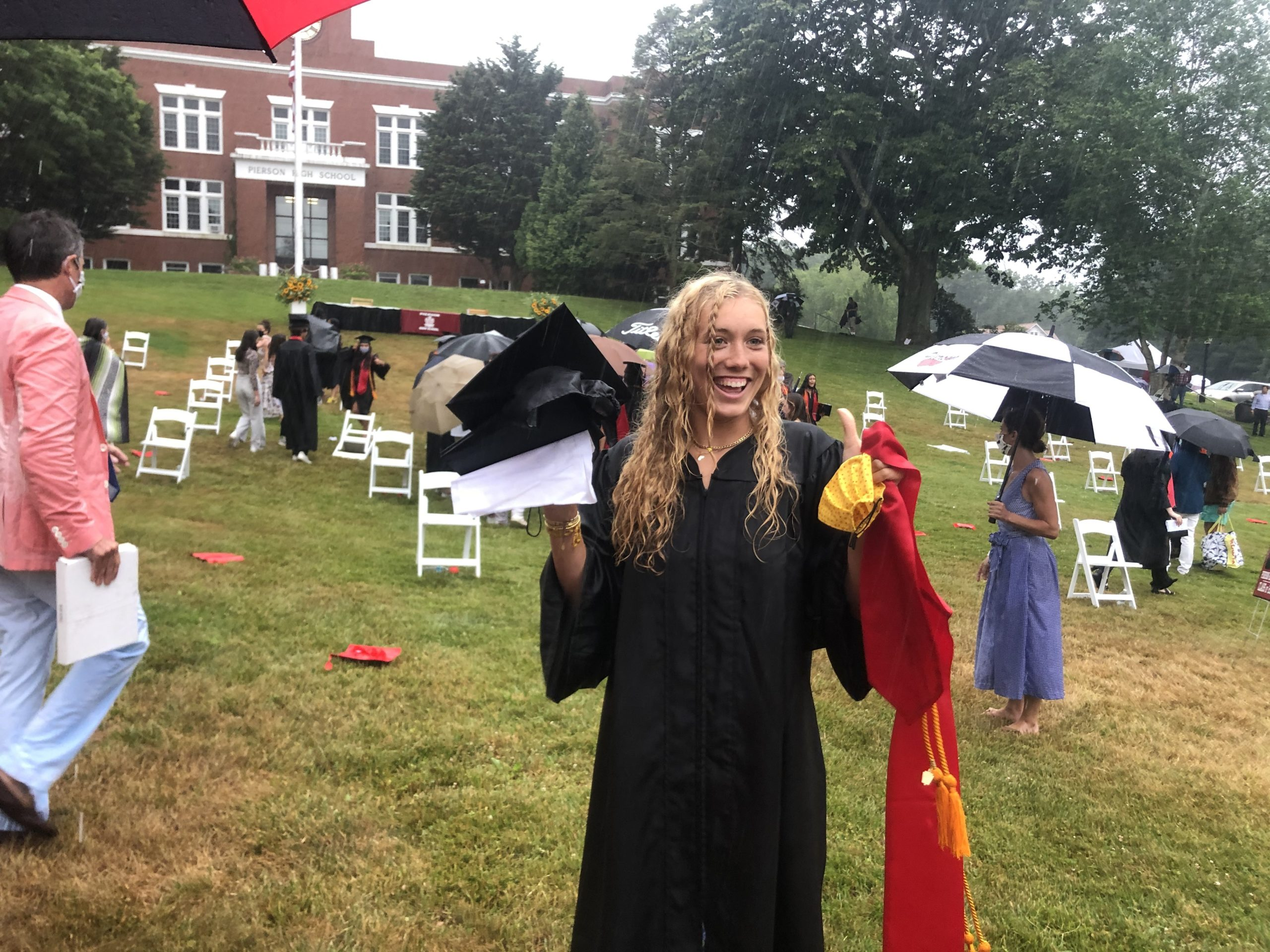 Cancer survivor Halle Kneeland dries off from a rainstorm after graduating from Pierson High School on June 27.