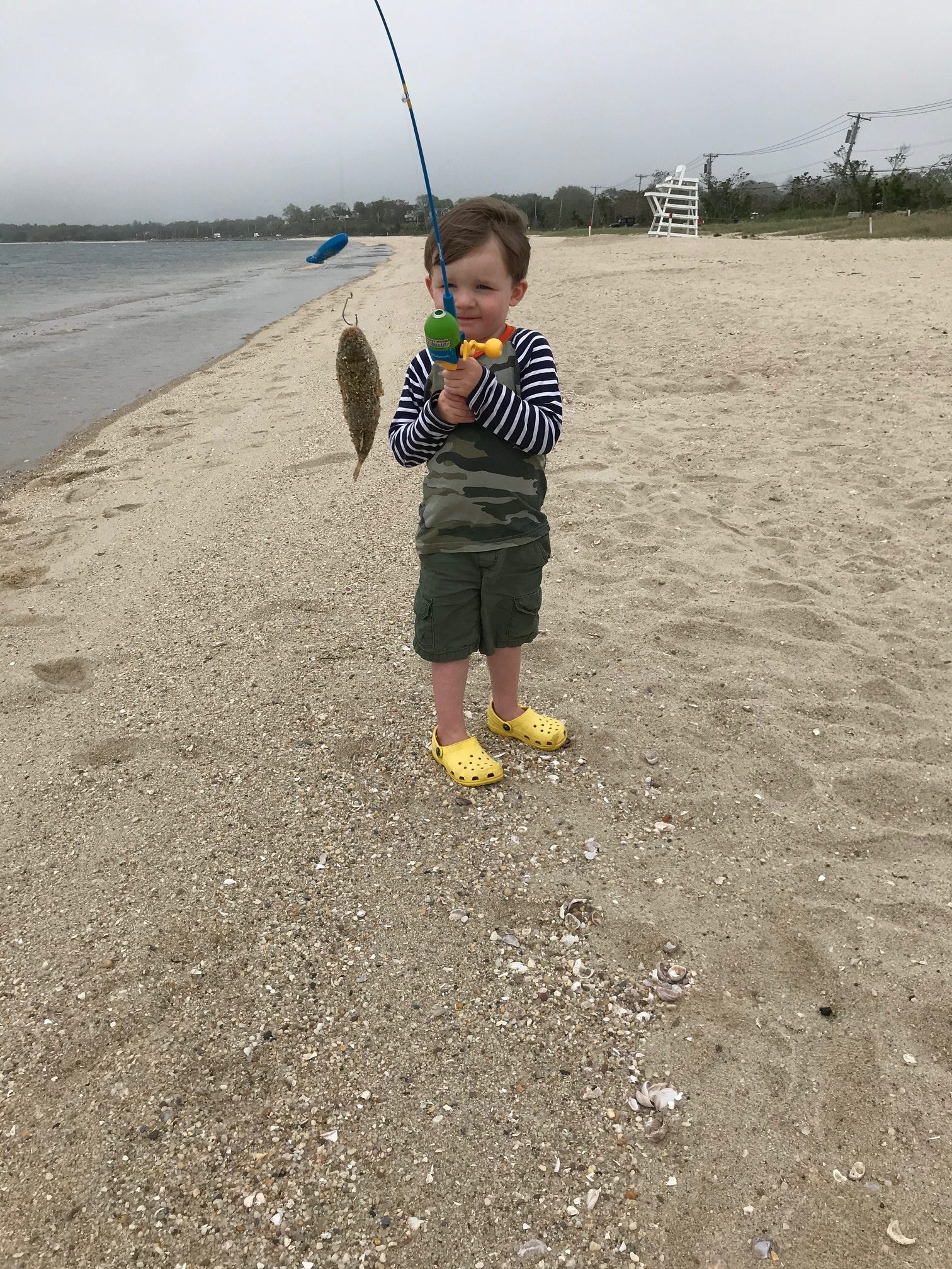 Three-year-old Henry Schubert caught his first fish on the first cast at Long Beach near the Bay Point home of his grandfather, Mark Hasllnger.