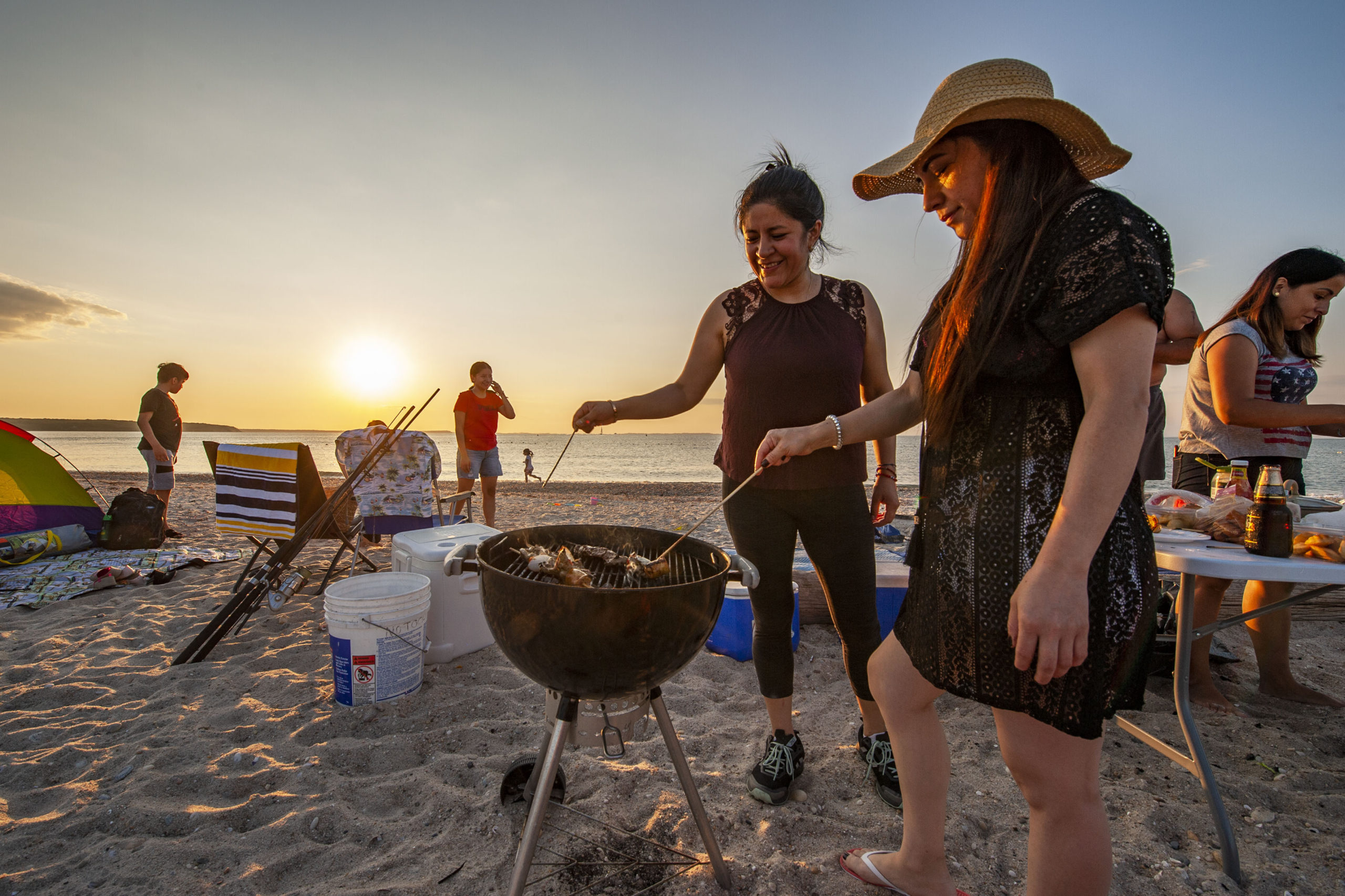 Nancy Vinueza cooks up some Shish Kebab on the grill as she joins friends and family in a July 4th celebration as the sun goes down at Maidstone Park Beach on Saturday evening.  MICHAEL HELLER