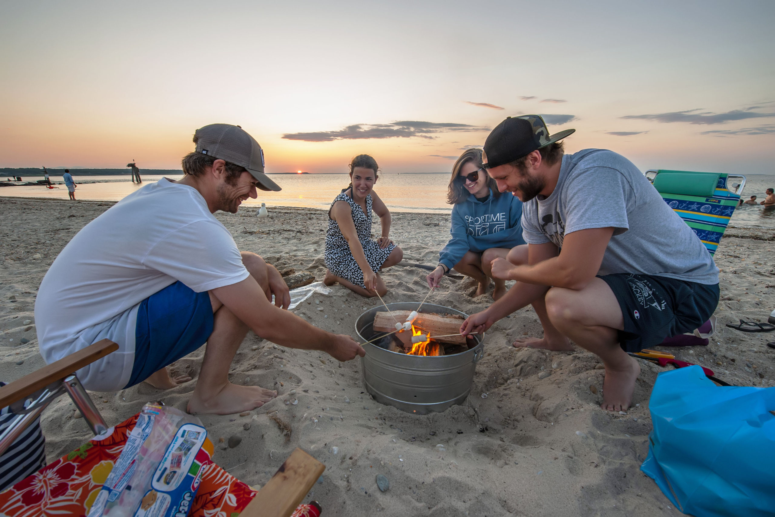 Randall Rush, Leanna DeMai, Lindsay DePointe and Tyler Jarvis roast marshmallows at their campfire as part of a July 4th celebration as the sun goes down at Maidstone Park Beach on Saturday evening.  MICHAEL HELLER