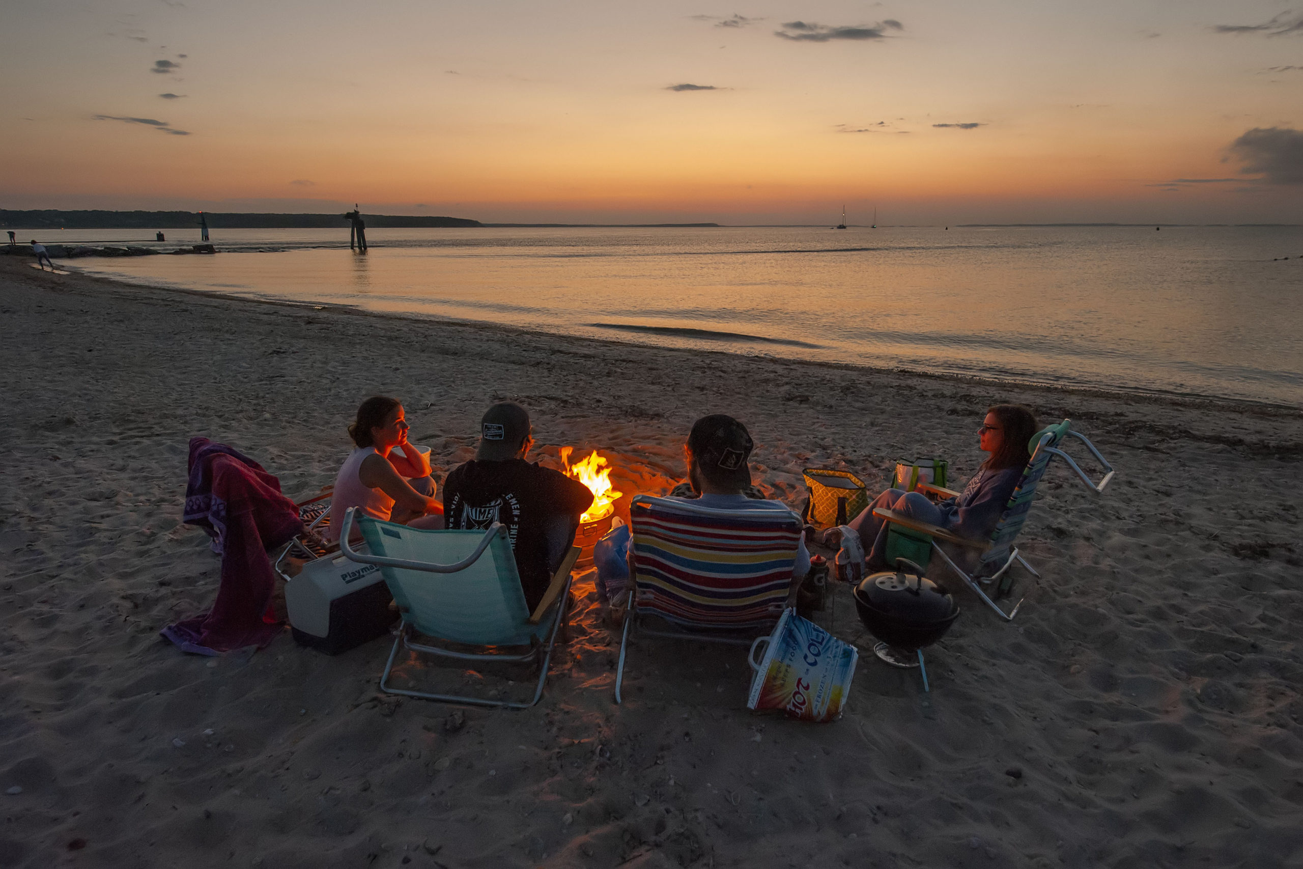 Randall Rush, Leanna DeMai, Lindsay DePointe and Tyler Jarvis enjoy a campfire as part of a July 4th celebration as the sun goes down at Maidstone Park Beach on Saturday evening.   MICHAEL HELLER