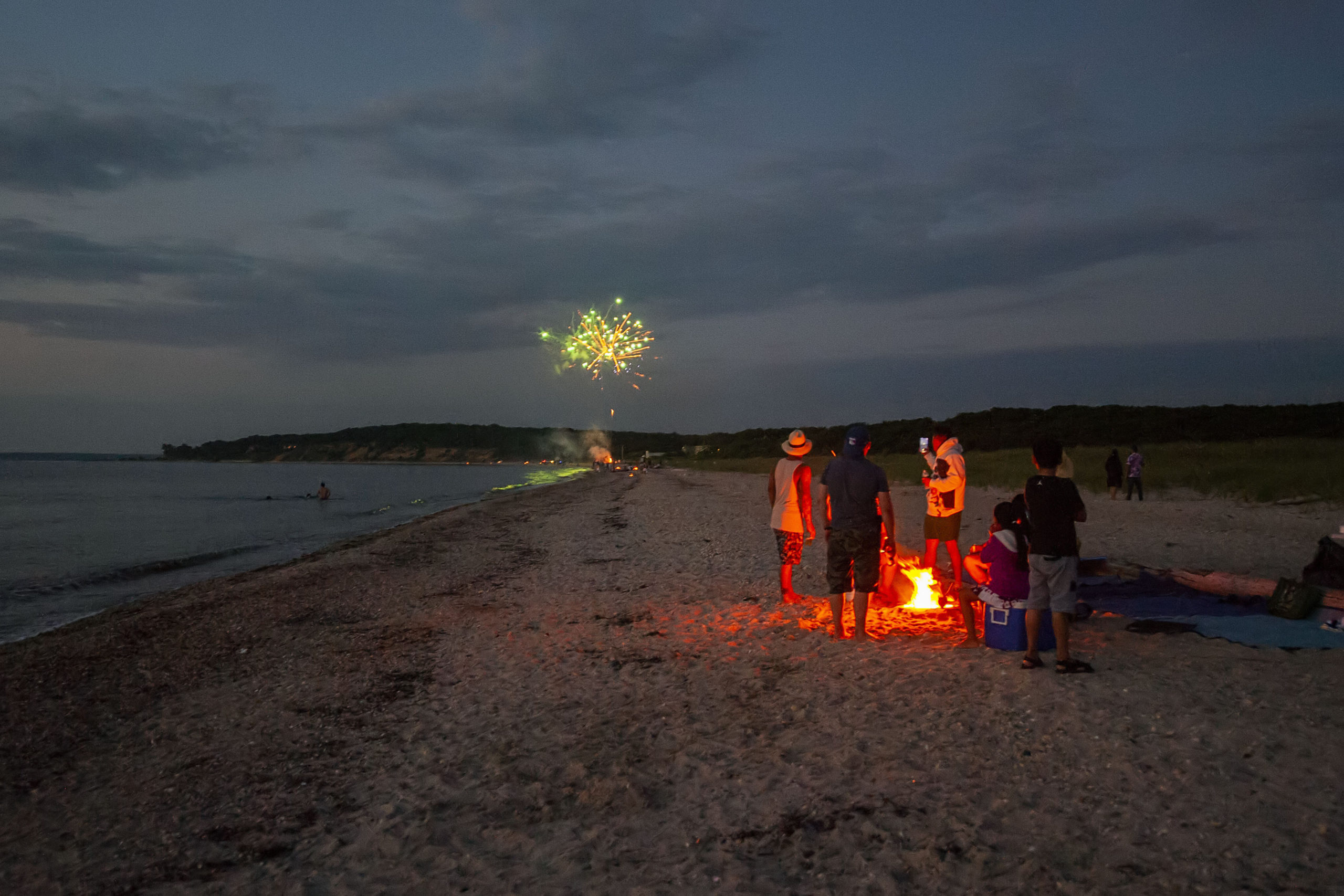 A family watches from around their campfire as another party sets off their own fireworks on the beach as part of a July 4th celebration as the sun goes down at Maidstone Park Beach on Saturday evening.    MICHAEL HELLER