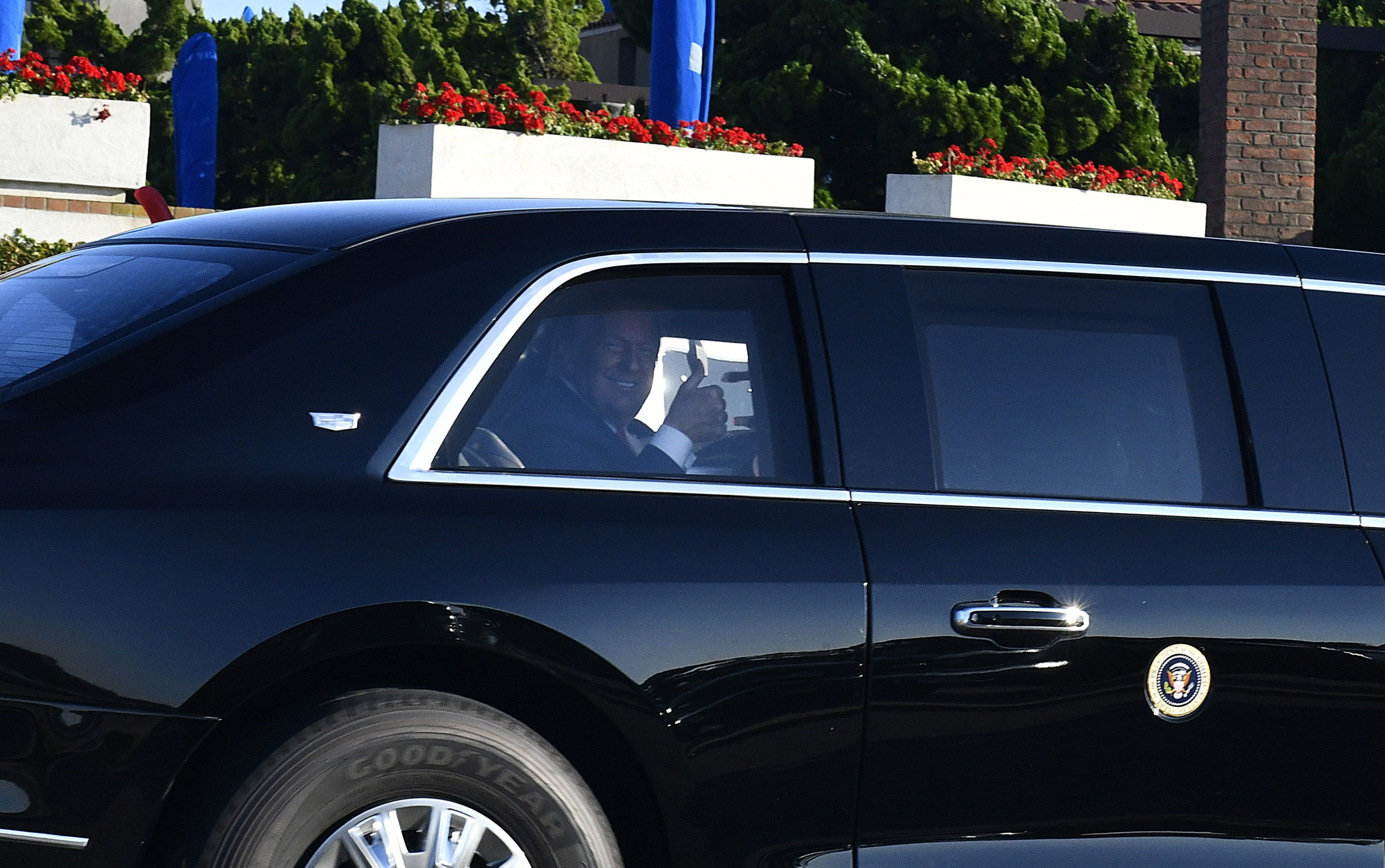 President Donald Trump gives the thumbs up on his way to a fundraising event on First Neck Lane in Southampton Village on Saturday afternoon.     DANA SHAW