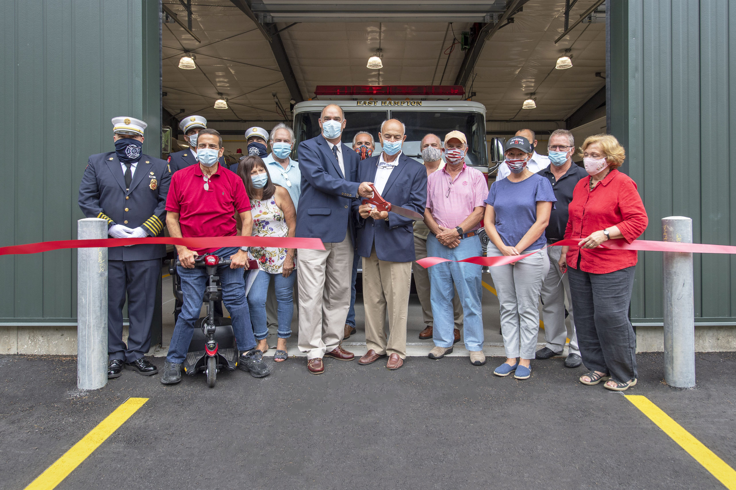 East Hampton Town Supervisor Peter Van Scoyoc and East Hampton Village Deputy Mayor Rick Lawler cut the ribbon during the ribbon-cutting ceremony for the new East Hampton Fire Department substation at 18 Old Northwest Road on Friday.   MICHAEL HELLER