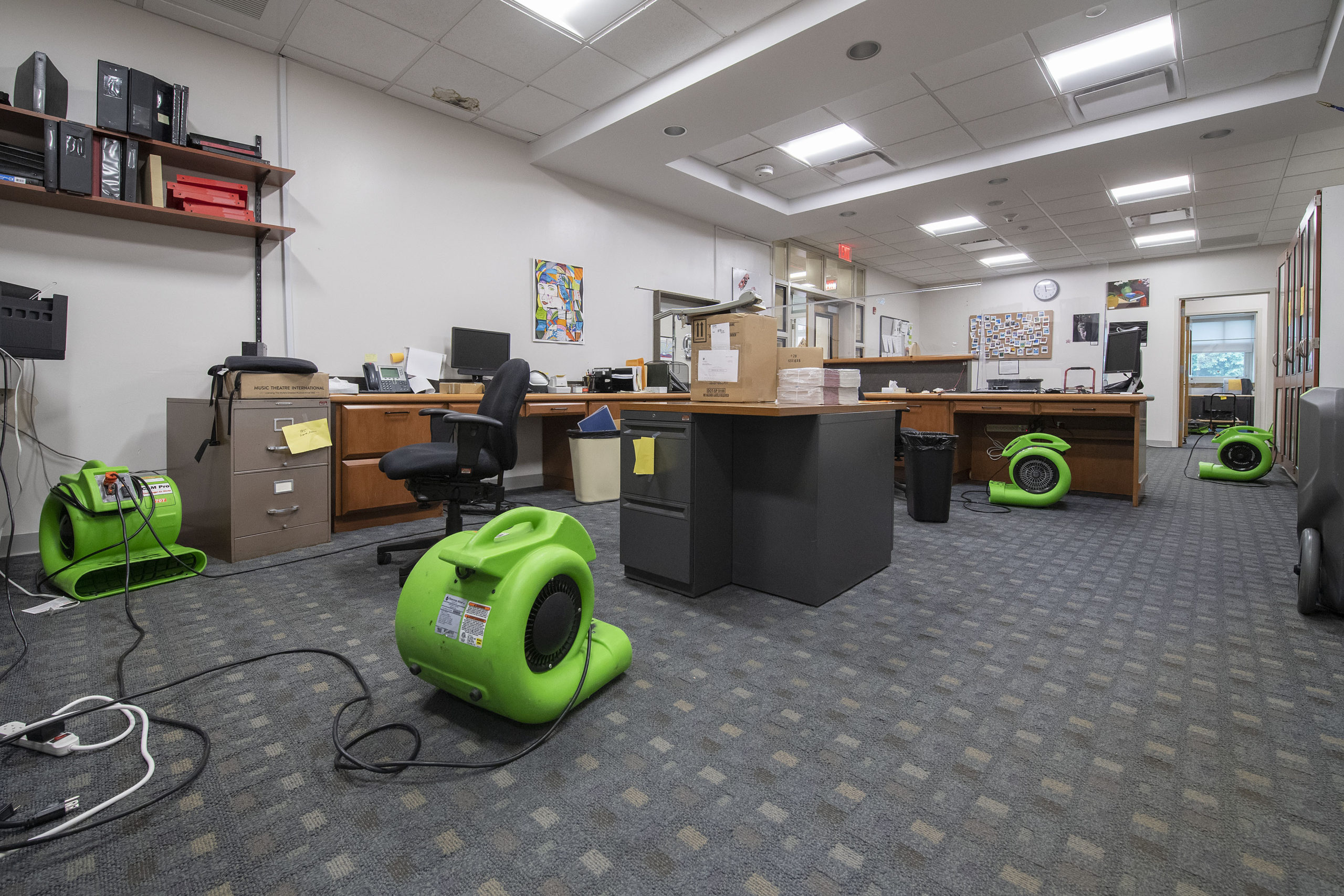 Fans have been placed throughout the East Hampton School District's administrative offices to help dry the carpet, which was flooded when a water pipe burst over the weekend. MICHAEL HELLER