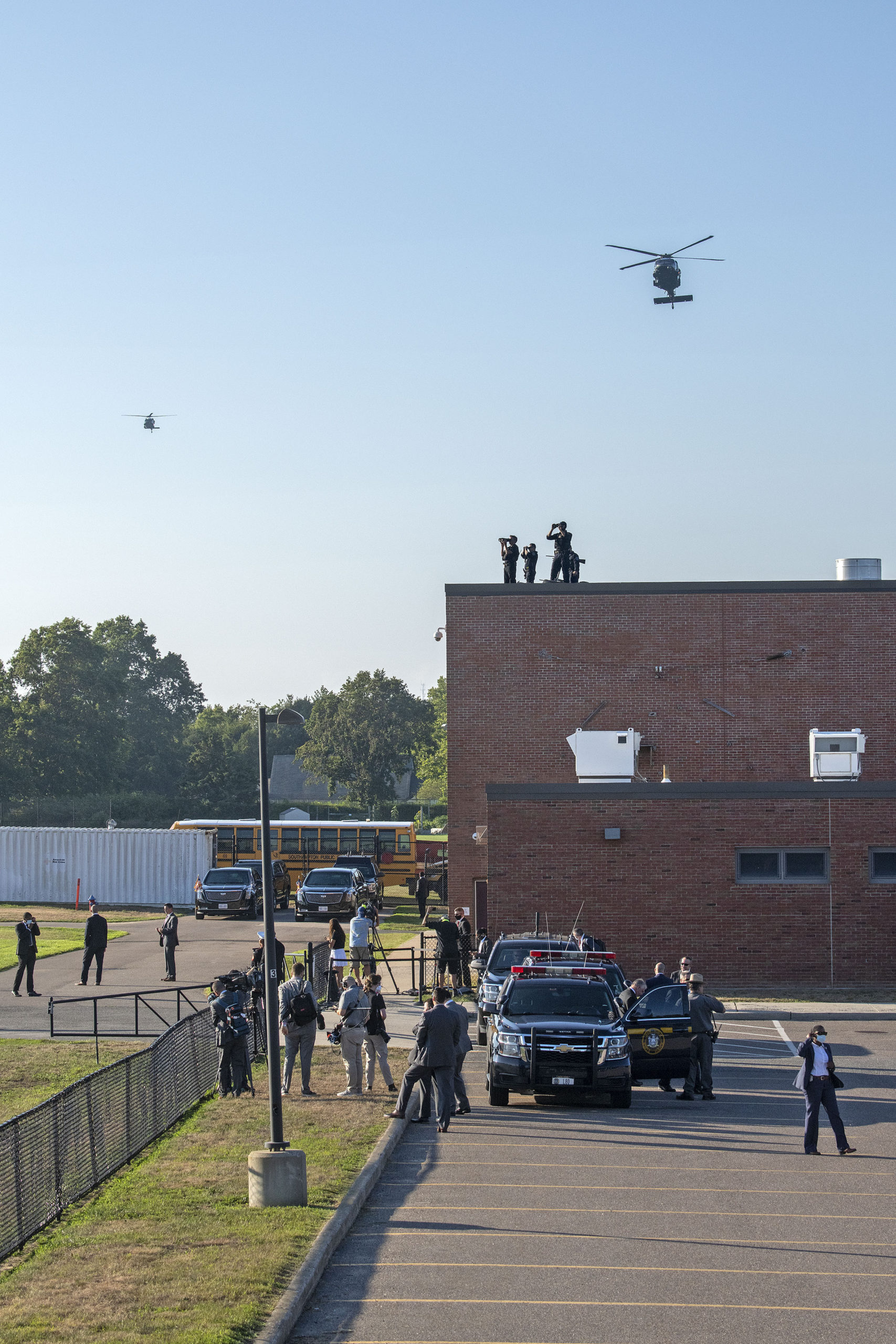 The presidential motorcade awaits as helicopters approach for a landing. Members of the Southampton Fire Department went on standby to provide fire protection as President Donald Trump arrived at the athletic fields behind Southampton High School during his visit to the Hamptons on Saturday.    MICHAEL HELLER