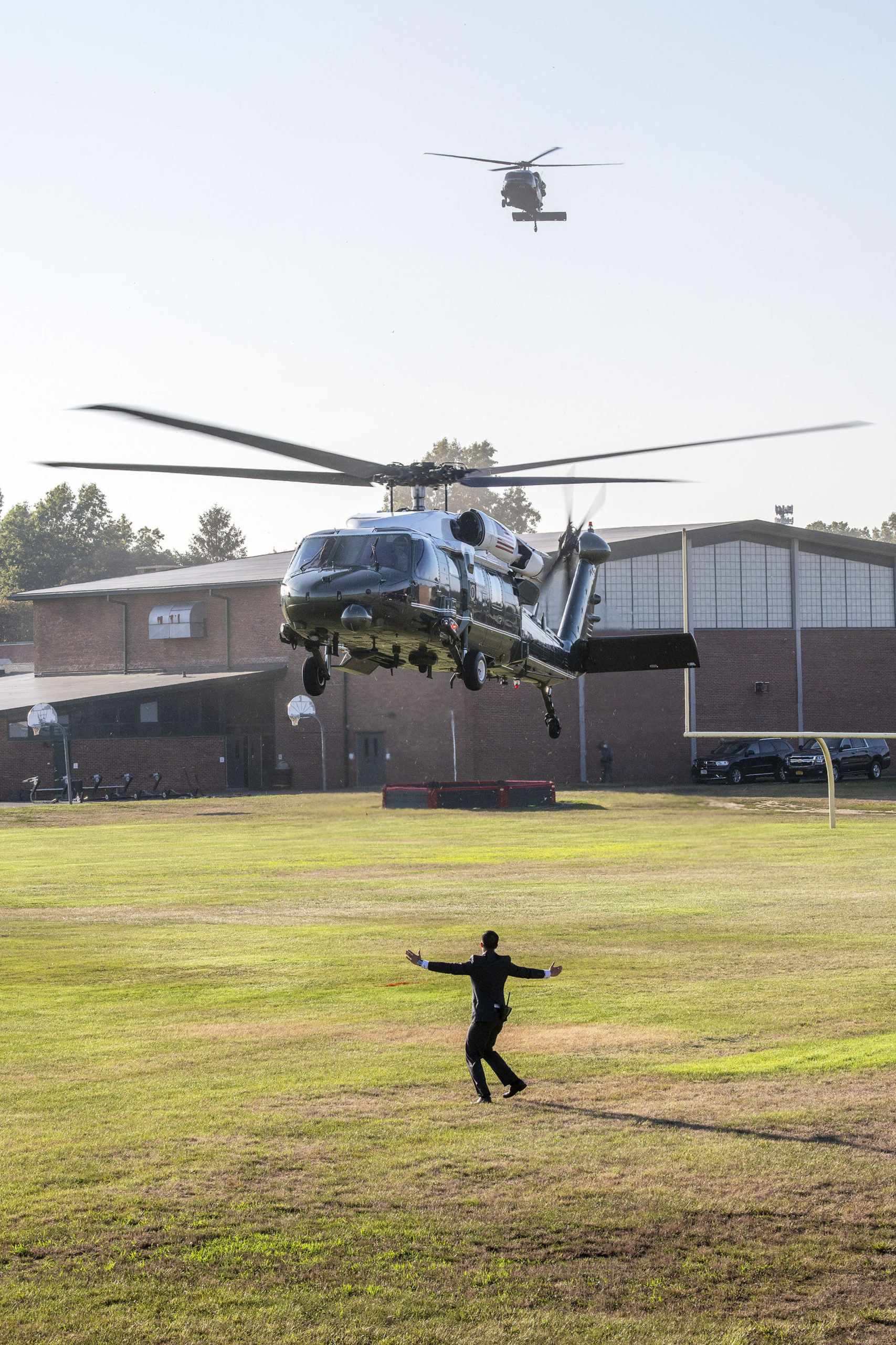 A plainclothes Marine guides one of the presidential Blackhawk helicopters as it lands. Members of the Southampton Fire Department went on standby to provide fire protection as President Donald Trump arrived and departed from the athletic fields behind Southampton High School during his visit to the Hamptons on Saturday.         MICHAEL HELLER