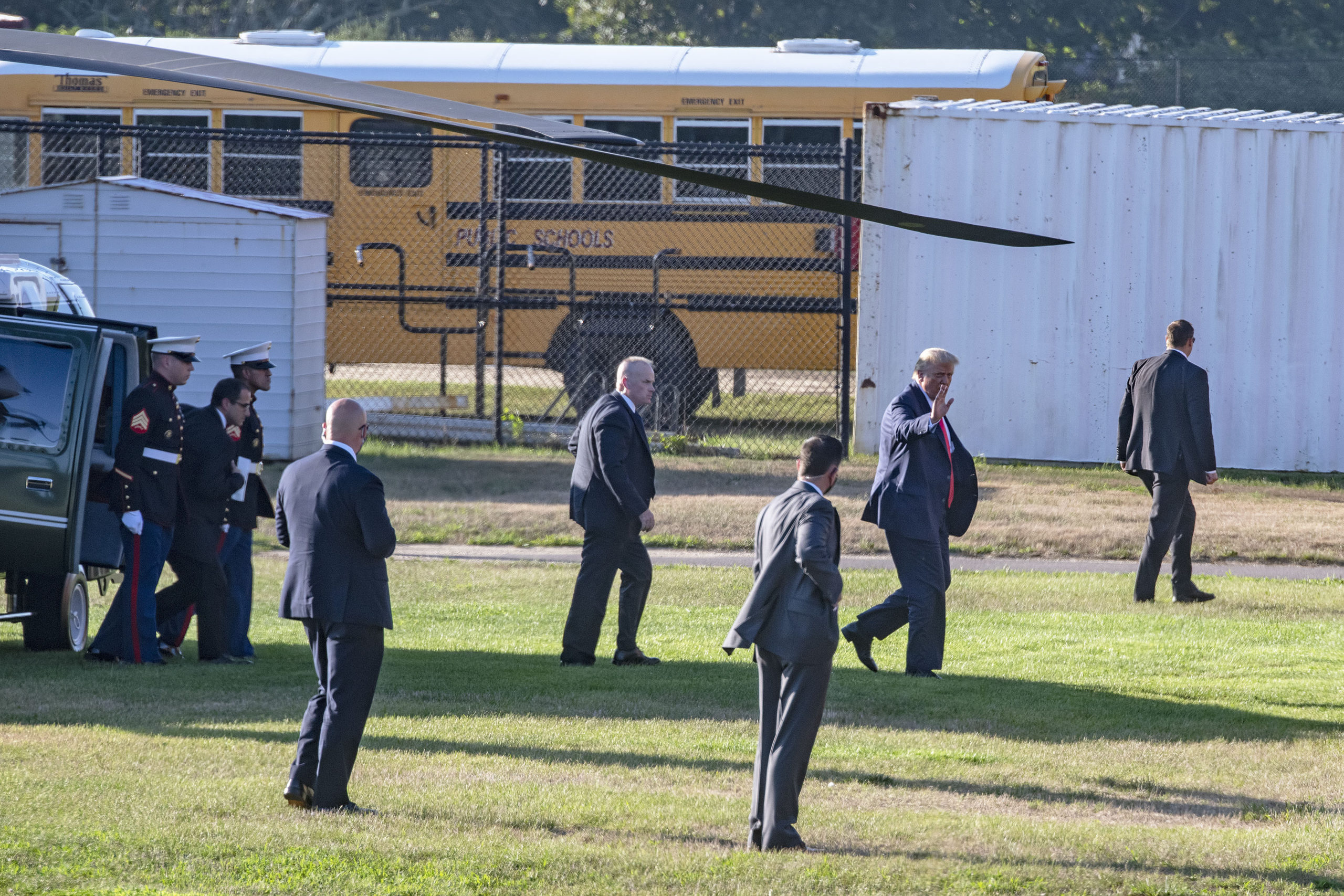 President Donald Trump waves as he walks toward his limousine after arriving via Marine helicopter at the athletic fields behind Southampton High School during his visit to the Hamptons on Saturday.   MICHAEL HELLER